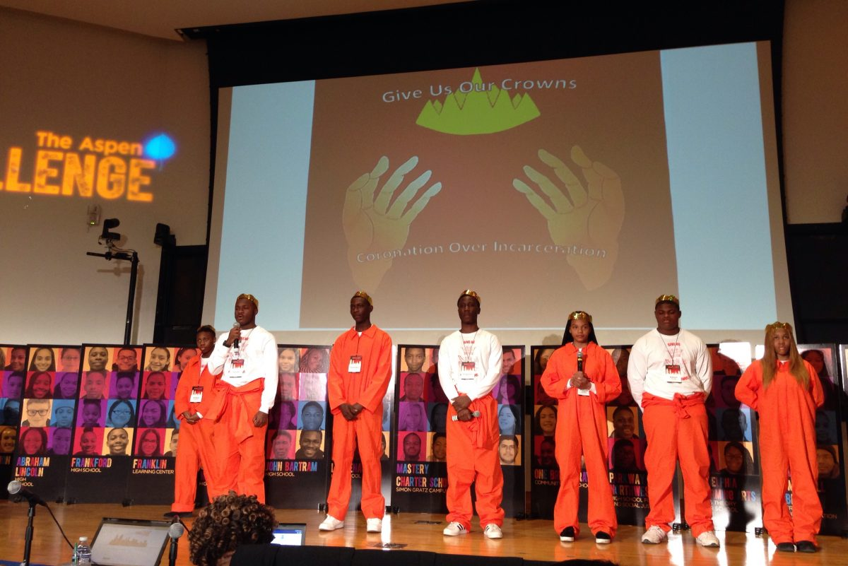 """Students from John Bartram High School present their solutions to the """"school-to-prison pipeline"""" while wearing prison jumpsuits at the Aspen Challenge on April 11, 2018."""
