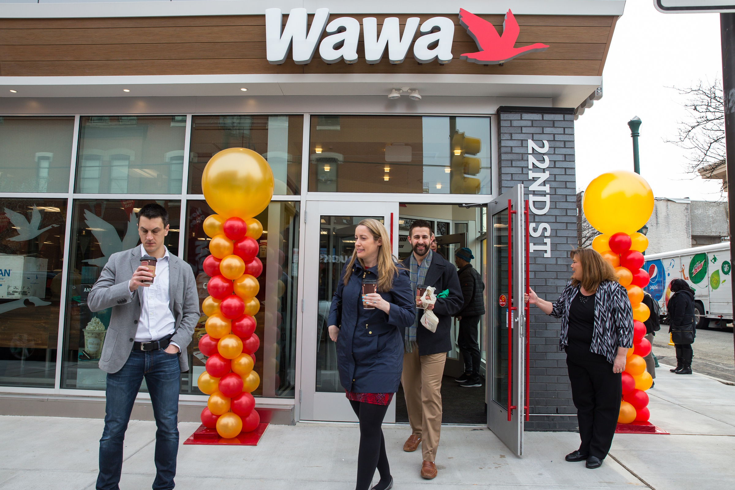 Visitors with free cups of coffee at the opening of the new WAWA, located at 2131 South Street.