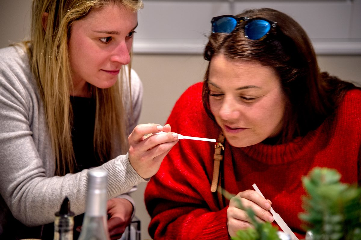 Mariel Levey (left) and Amanda Shor (right) sniff scents as they attend candle-making party with friends, at the new Philadelphia experience: Wax and wine, where one drinks wine and makes candles.