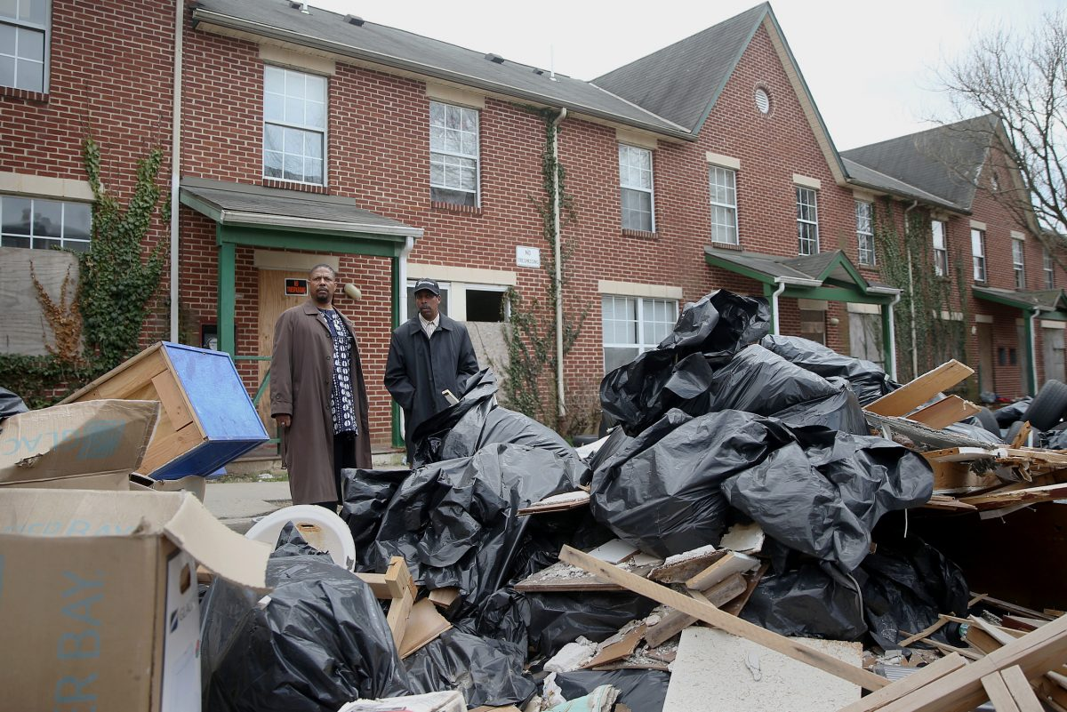 Germantown activists  Ted Stones (left) and Keith Q. Schenck navigate the piles of trash at a shuttered affordable housing development built by former Germantown Settlement CEO Emanuel Freeman.