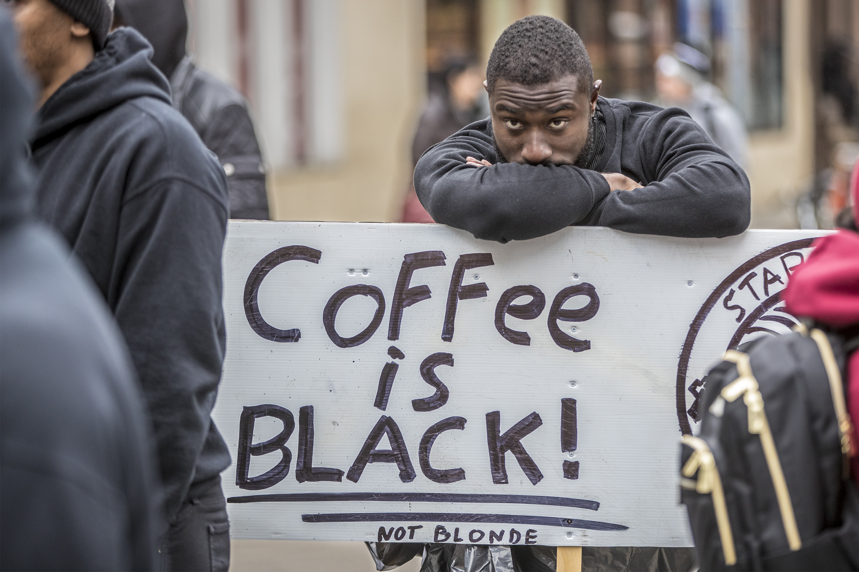 Jack Willis leans over his sign and takes in the scene at the protest of the Starbucks at 18th and Spruce Streets Sunday.