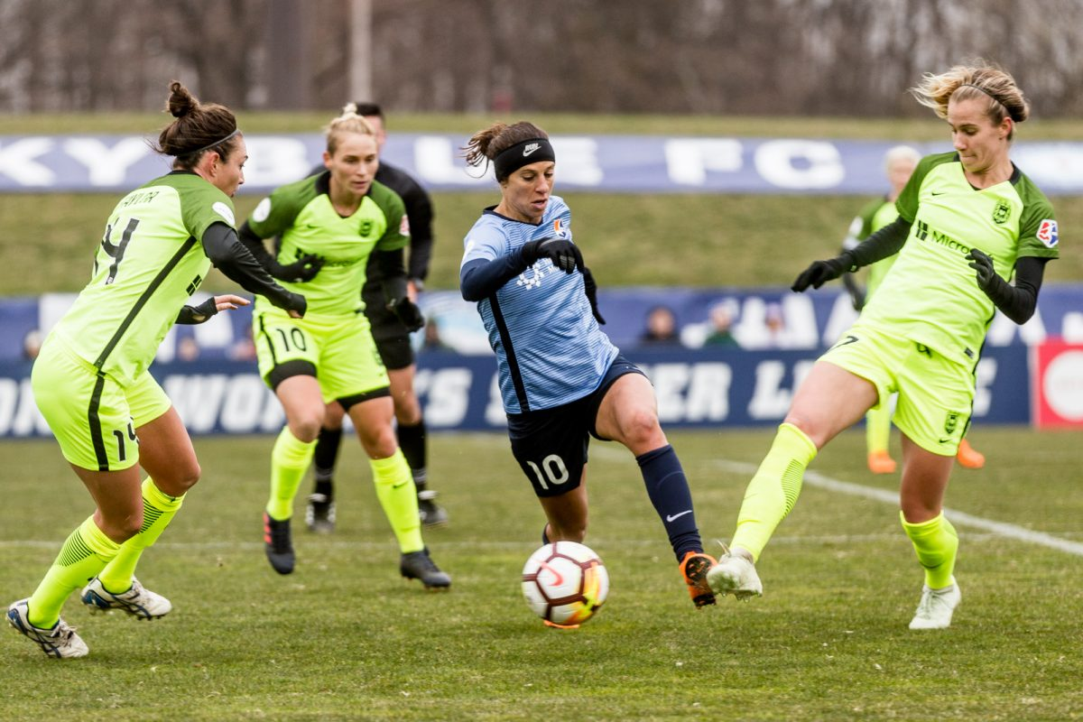 Carli Lloyd dribbles between three Seattle Reign players during her home debut for Sky Blue FC at Rutgers´ Yurcak Field.