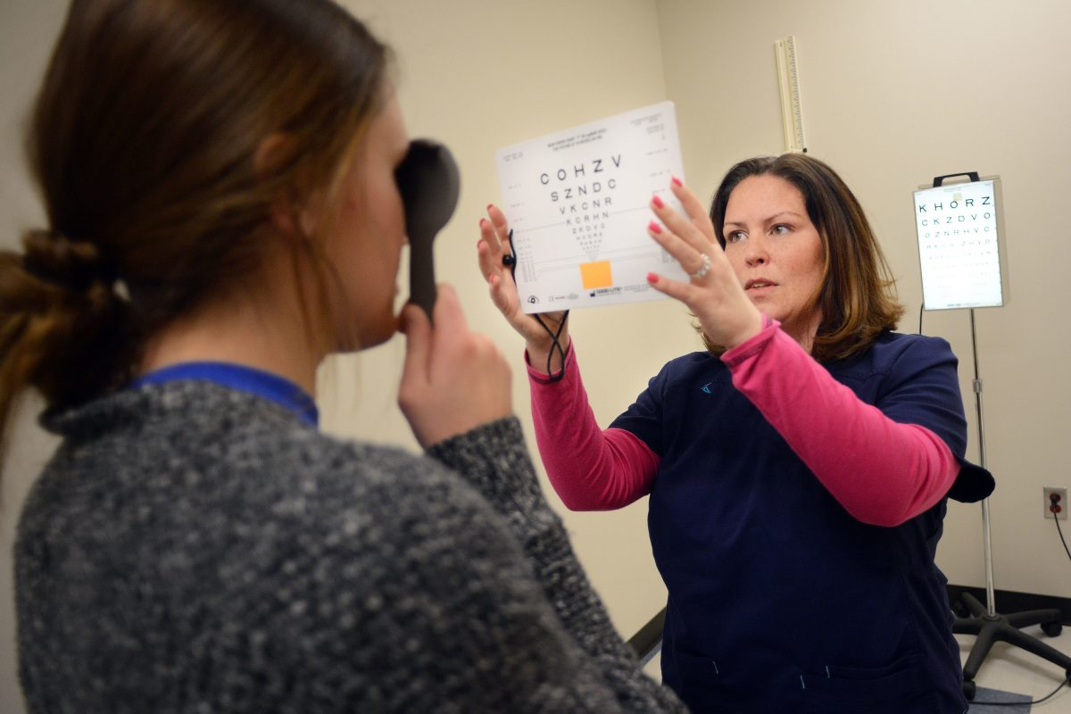Bensalem High School Nursing Coordinator Jamie Thim gives an eye test to a 10th grade student.