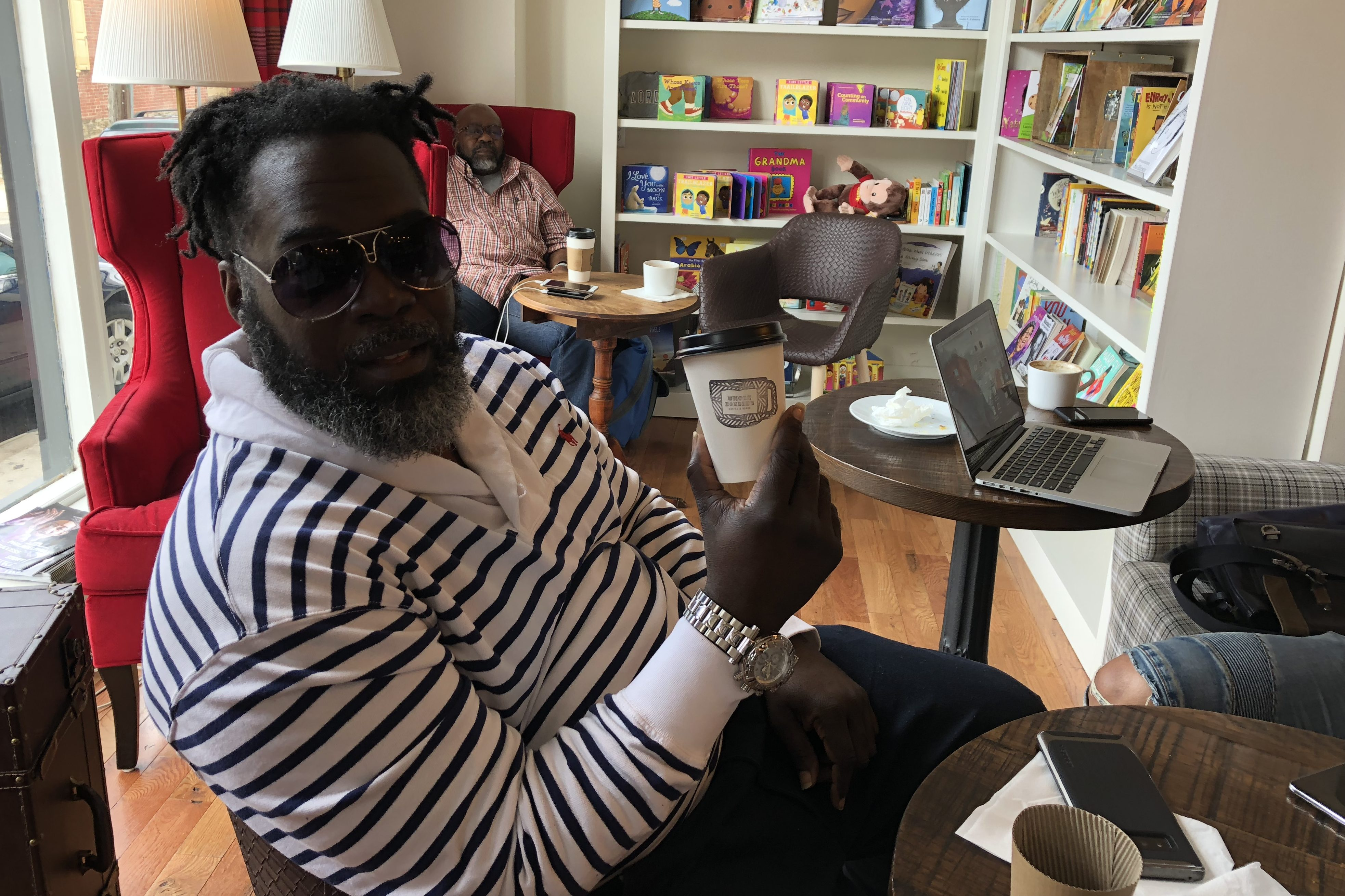 Eli White proudly shows off his coffee cup at Uncle Bobbie´s, a black-owned Germantown bookstore-cafe.