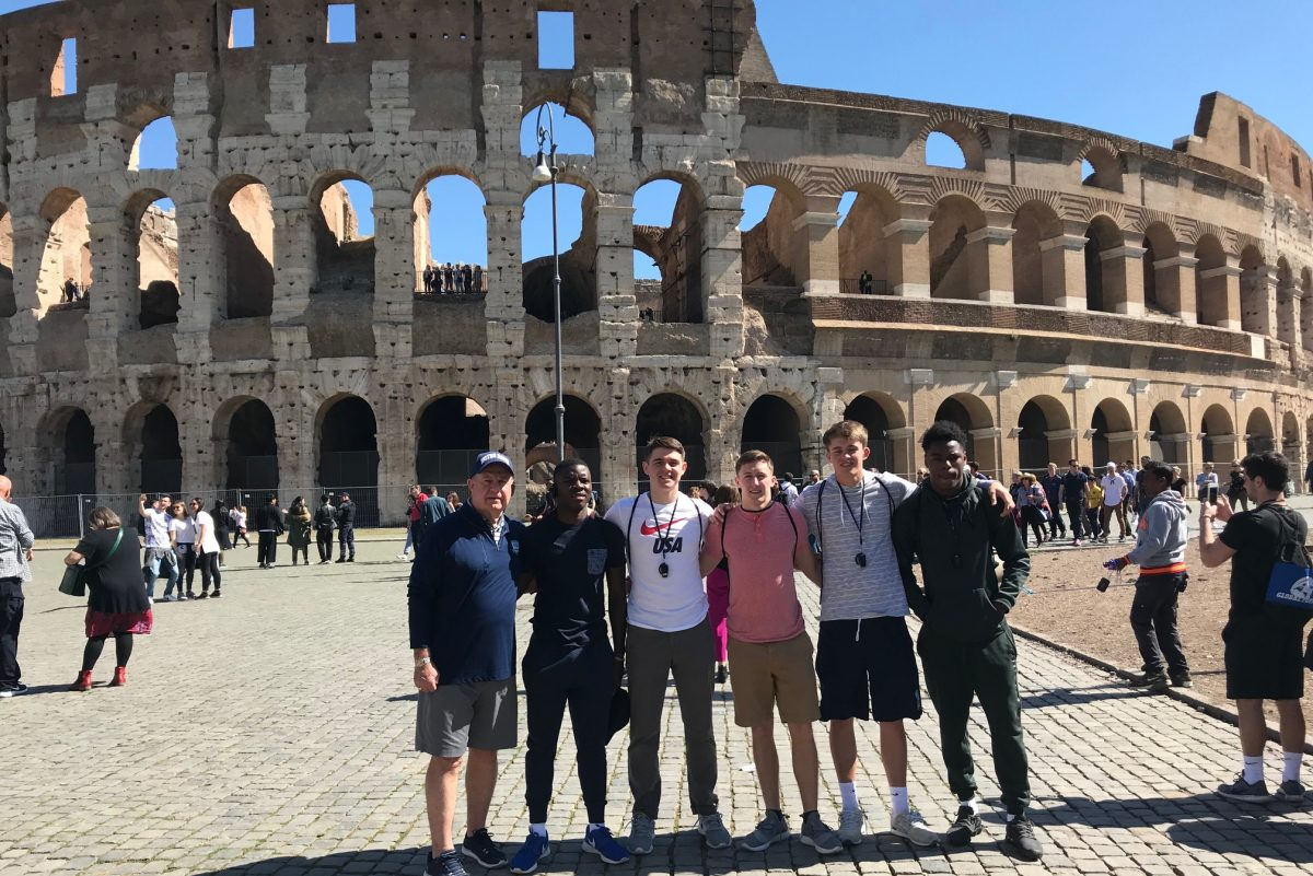 Team Stars & Stripes  coach Bill Gallagher (far left) poses with (from left) Penn Charter's John Washington and Owen Peters, Father Judge's Sean Cunningham, Springside Chestnut Hill's Jack Elliott, and Cheltenham's Jordan Gyabaah in front of the Coliseum.