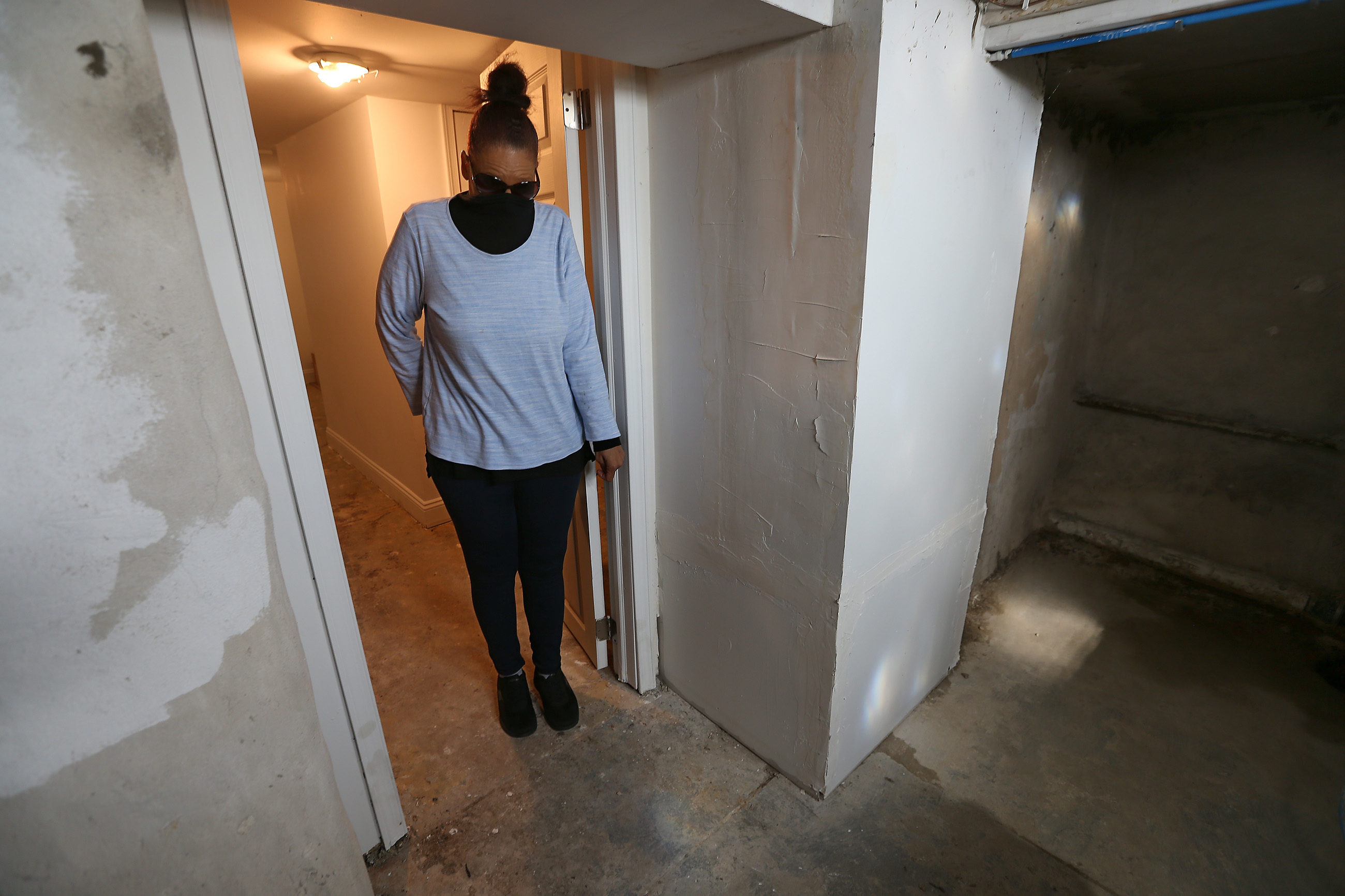 Linda Watson covers her nose because she can´t stand the smell after sewage backed up into the basement of the house she is renting in the Port Richmond section of Philadelphia. Watson´s landlord sent her an eviction notice after she withheld rent due to the conditions.