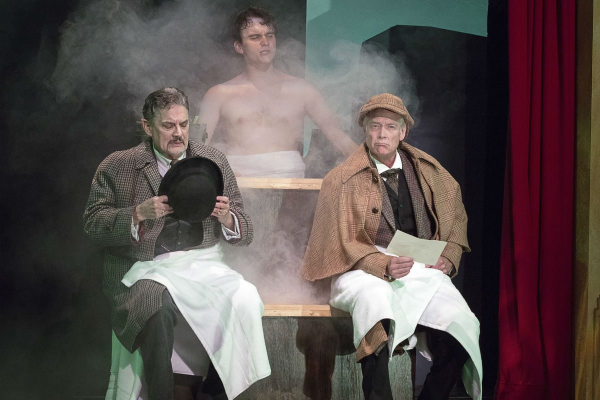 """(Left to right:) Watson (Carl N. Wallnau), and Sherlock Holmes (Greg Wood) discover Sir Henry Baskerville (Jacob Dresch) in a steam bath in the Pennsylvania Shakespeare Festival's production of """"The Hound of the Baskervilles."""""""