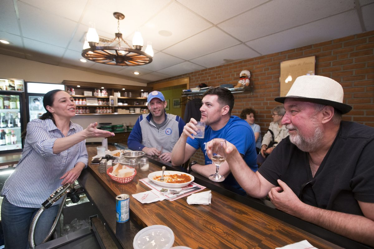Bartender Mary Ludovici, left, jokes with some customers at the bar at Villa Di Roma.