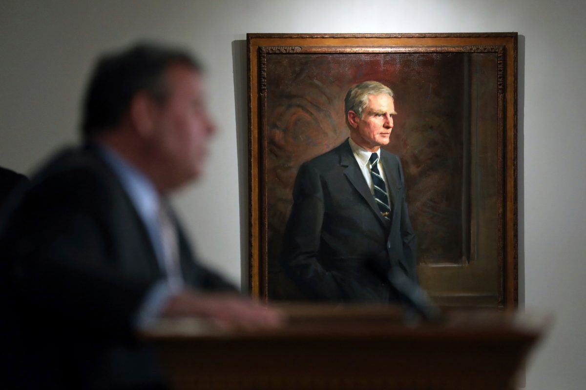 In this July 3, 2017, file photo, former New Jersey Gov. Brendan Byrne´s portrait hangs nearby as New Jersey Gov. Chris Christie speaks in Trenton, N.J. The official portrait of Christie, a two-term Republican governor, by Australian artist Paul Newton will cost $85,000, The Record reported Thursday, April 19, 2018, more than taxpayers shelled out for paintings of his three Democratic predecessors combined.