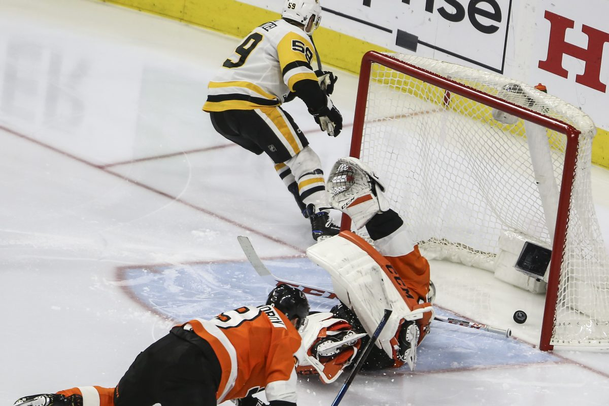 Ivan Provorov and goaltender Michal Neuvirth are left sprawled on the ice as Jake Guentzel celebrates one of the four goals he scored on Sunday night.
