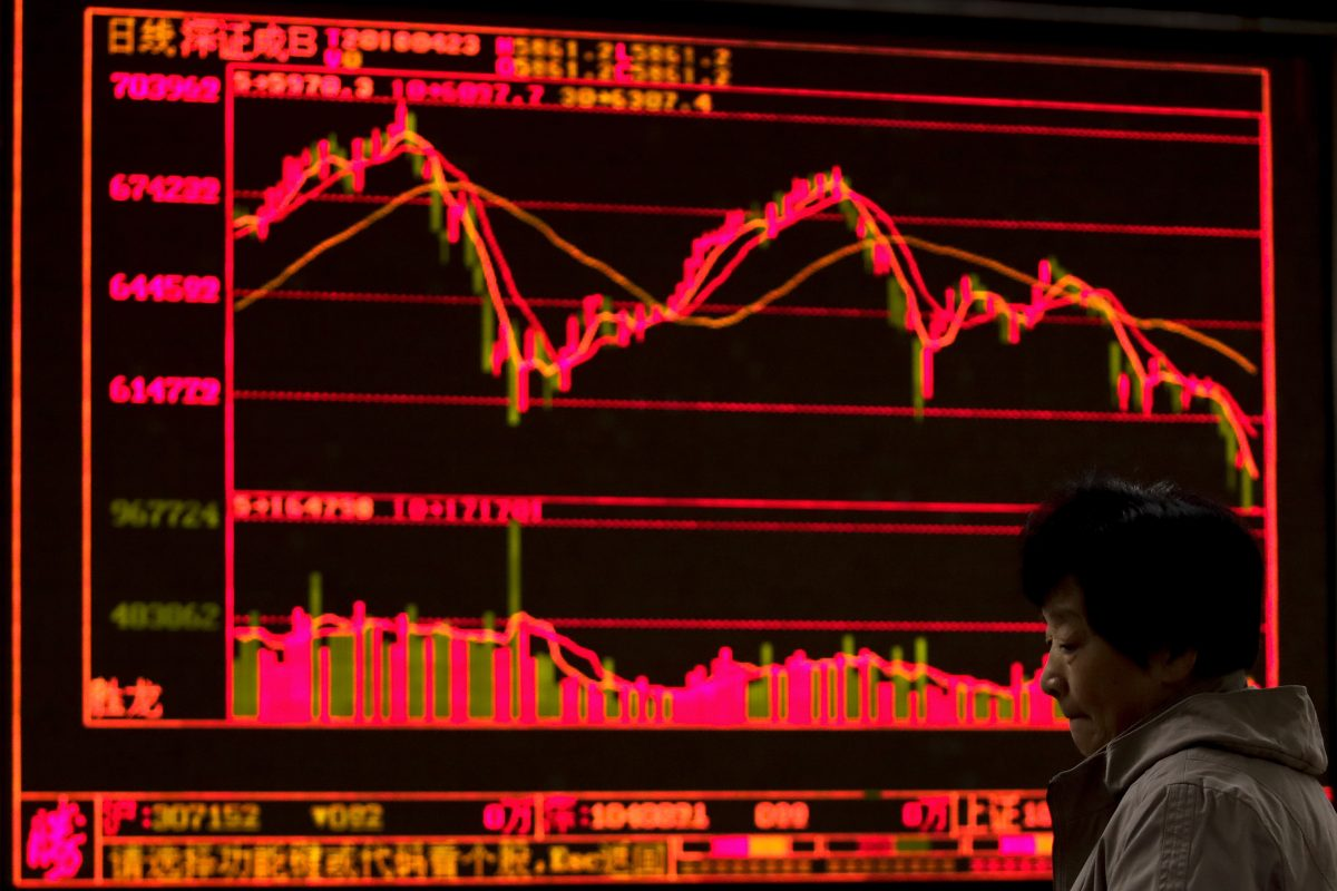 A woman reacts at a brokerage house displaying stock trading index in Beijing, Monday.