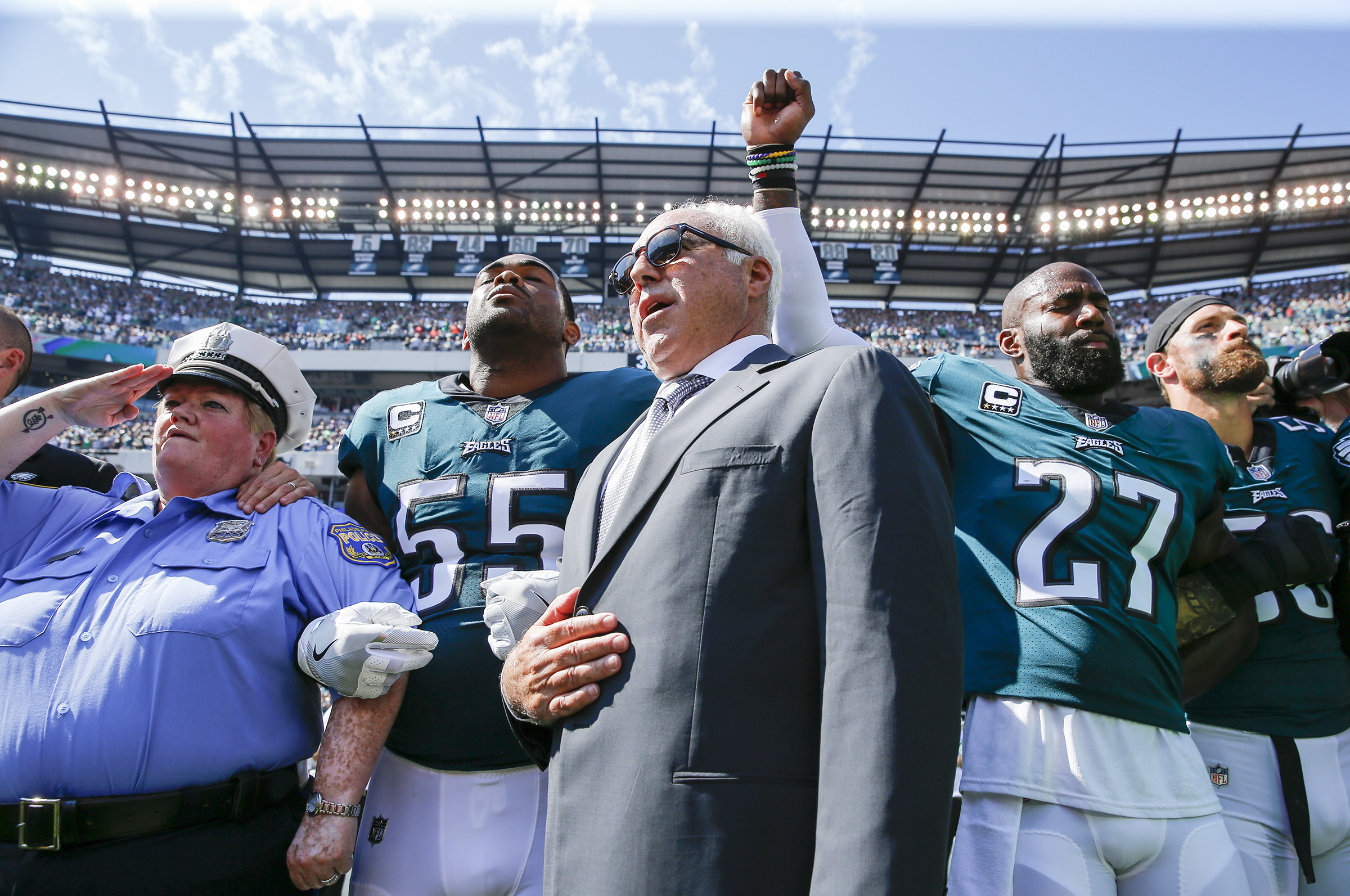 Eagles owner Jeffrey Lurie stands with Eagles defensive end Brandon Graham and strong safety Malcolm Jenkins during the National Anthem. Lurie has been a critic of President Trump.