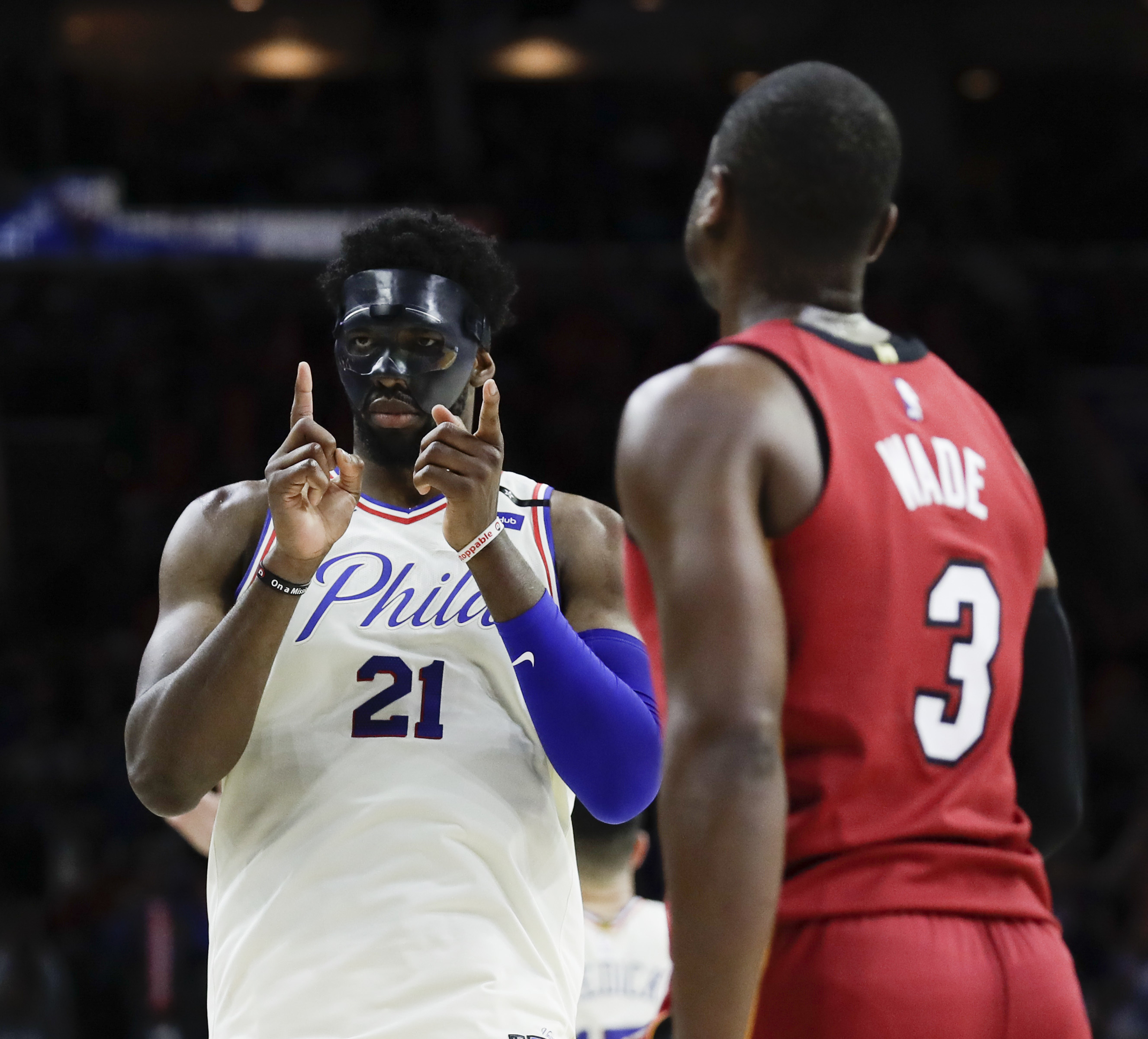 Sixers center Joel Embiid celebrates as the Sixers close out the Heat on Tuesday as Dwyane Wade, right, watches.