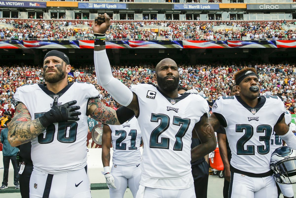 The Eagles' Malcolm Jenkins raises his fist in protest with teammates Chris Long (left) and Rodney McLeod during the national anthem before a September 2017 game.