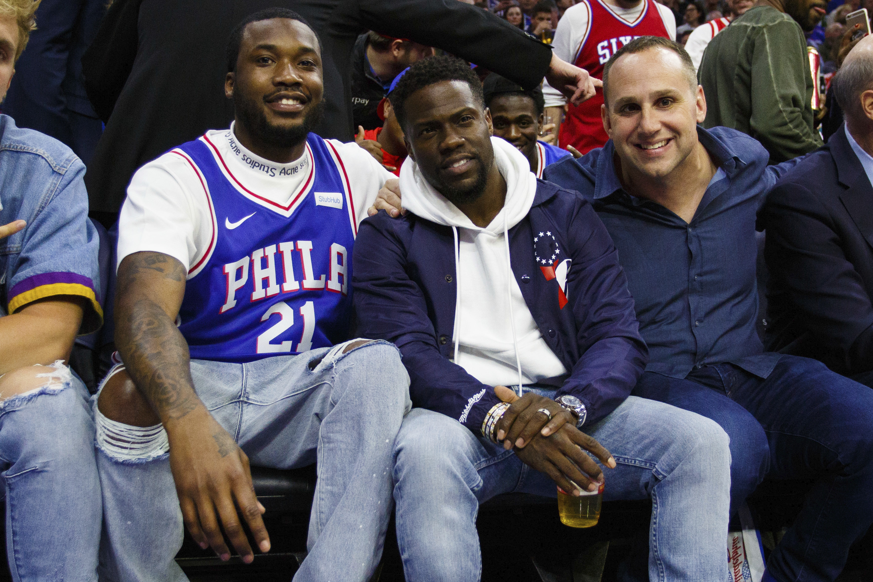Rapper Meek Mill, left, looks on with actor Kevin Hart, center, and 76ers´ co-owner Michael Rubin, right, during the first half in Game 5 of a first-round NBA basketball playoff series between the Miami Heat and the Philadelphia 76ers, Tuesday, April 24, 2018, in Philadelphia. The 76ers won 104-91. (AP Photo/Chris Szagola)