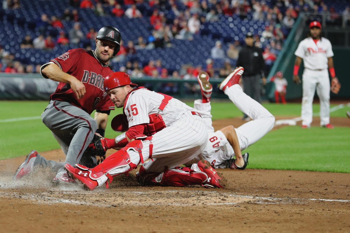 Andrew Knapp, center, of the Phillies tags out AJ Pollock of the Diamondbacks at home after Jake Arrieta, right, of the Phillies dove to flip the ball to him in the 4th inning on April 25, 2018.