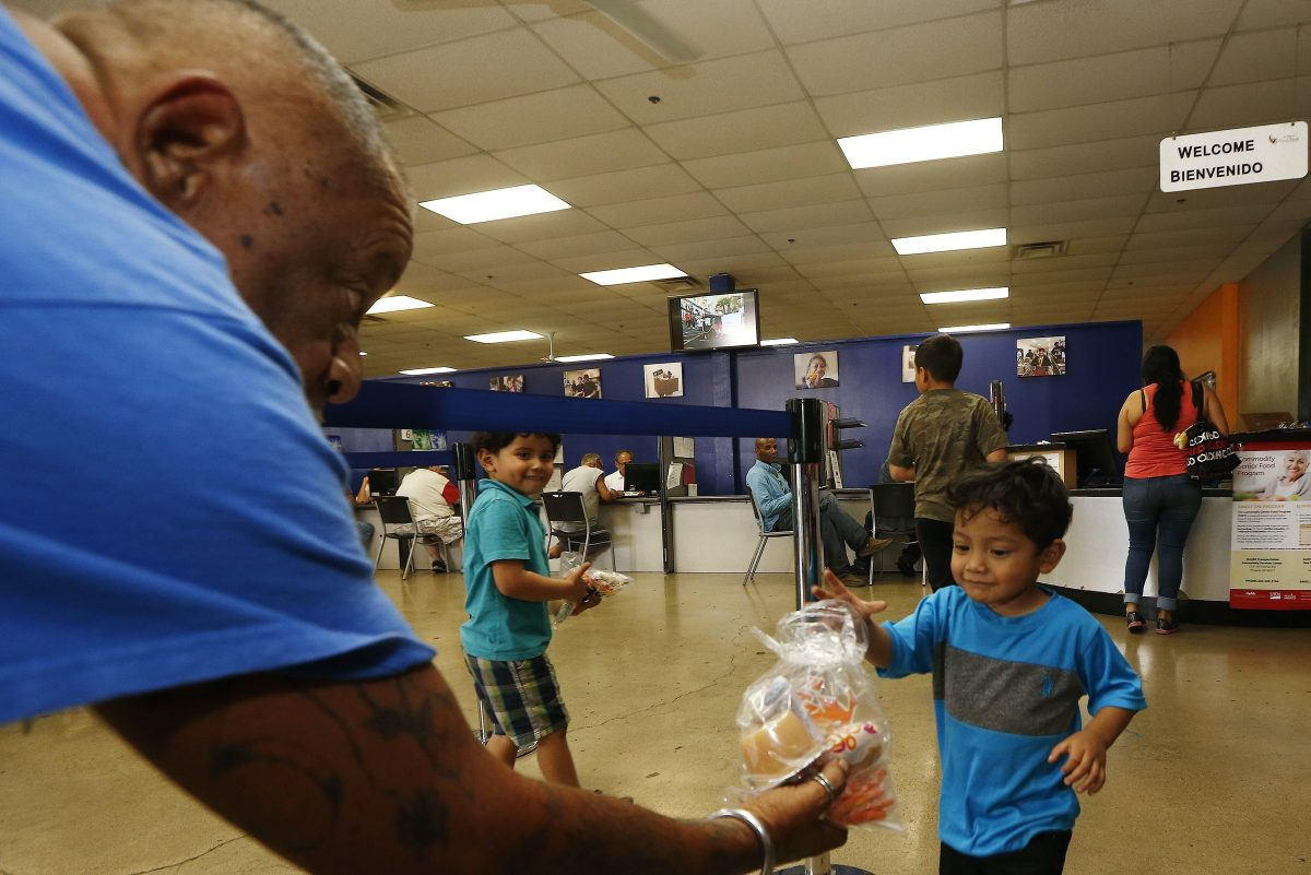 Volunteer Monroy Martinez, left, hands out a free to-go lunch to a young boy at the St. Mary´s Food Bank Alliance in Phoenix.