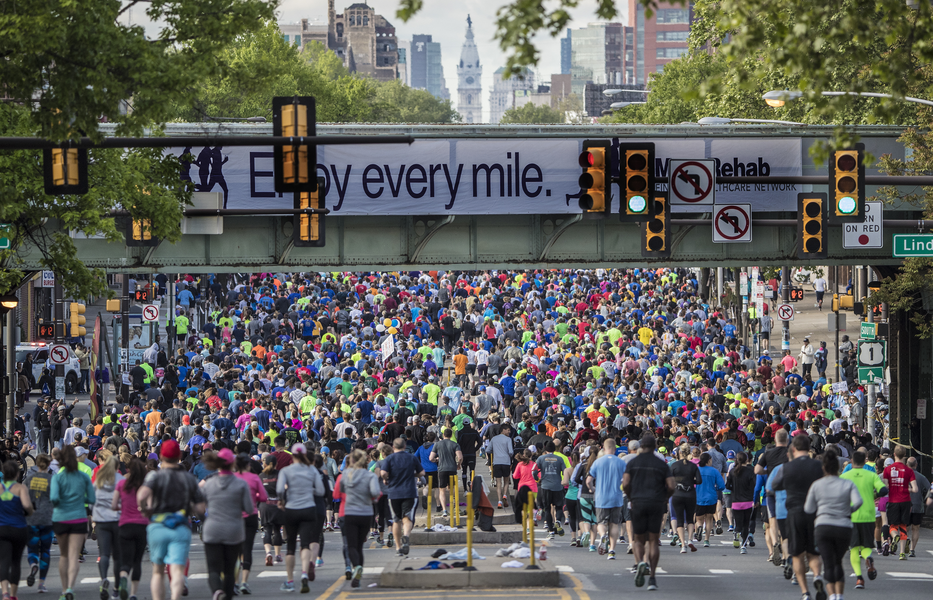 A mass of runners make their way toward City Hall, in the background, as they begin the Broad Street Run and run under a roialroad trestle bridge on their way to the Navy Yard in South Philadelphia. The Broad Street Run starting line is at Broad Street and W. Fisher Avenue. The race ends approximately one-quarter mile inside the main gate of the Philadelphia Navy Yard, at the southern end of Broad Street.