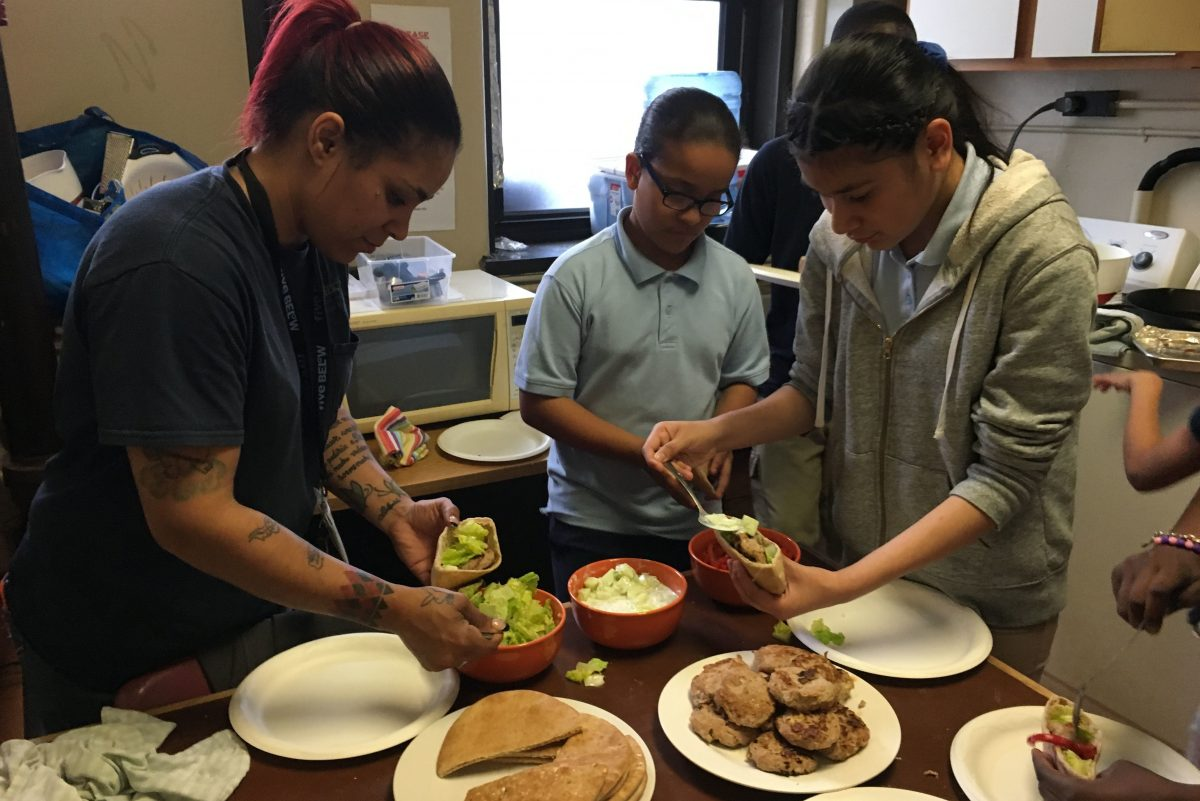 Juliana Marte (left), mother of cooking student Chris Marte, adds garnishes to her Greek turkey burger as Keisi Cedano and Yarethzy Campos prepare burgers for their guests at the last cooking class and party at Cramer Elementary School in Camden.