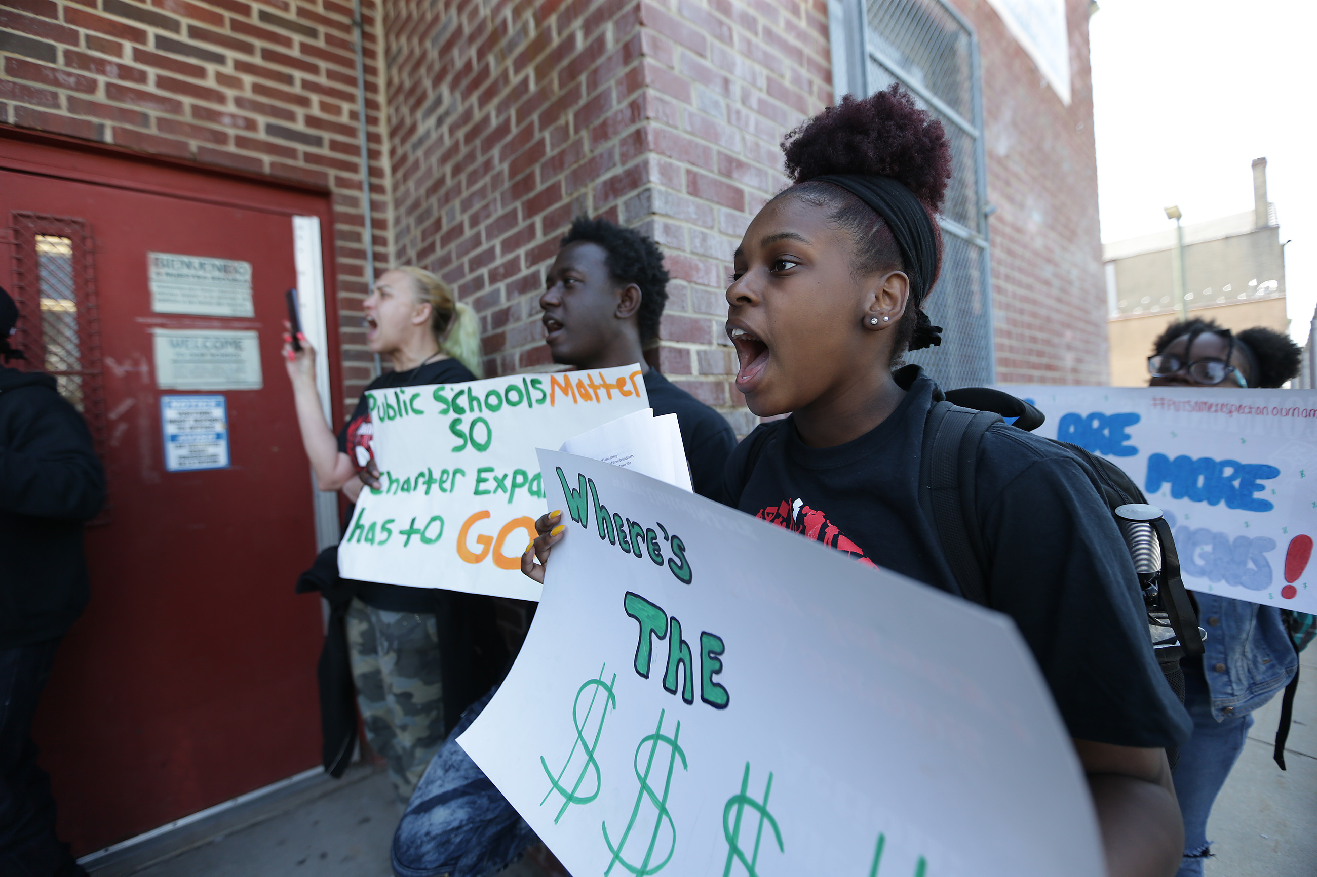 Lanasia Robinson, 16, at right, who is a member of New Jersey Communities United, protests outside the Camden City Board of Education Administration Building in Camden.