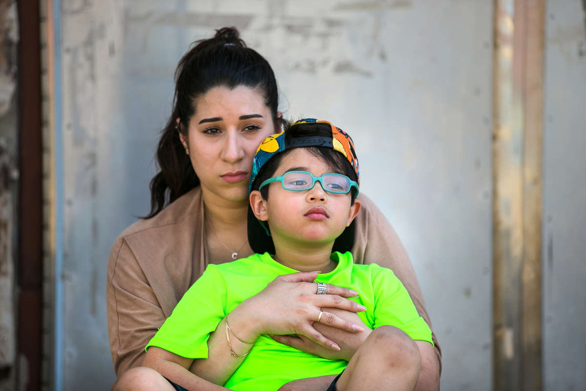 Cristine Pagan, back, holds her six-year-old son Dean Pagan, front, Wednesday, May 2, 2018, at a playground in Philadelphia. Dean was severely lead poisoned at Comly Elementary School.