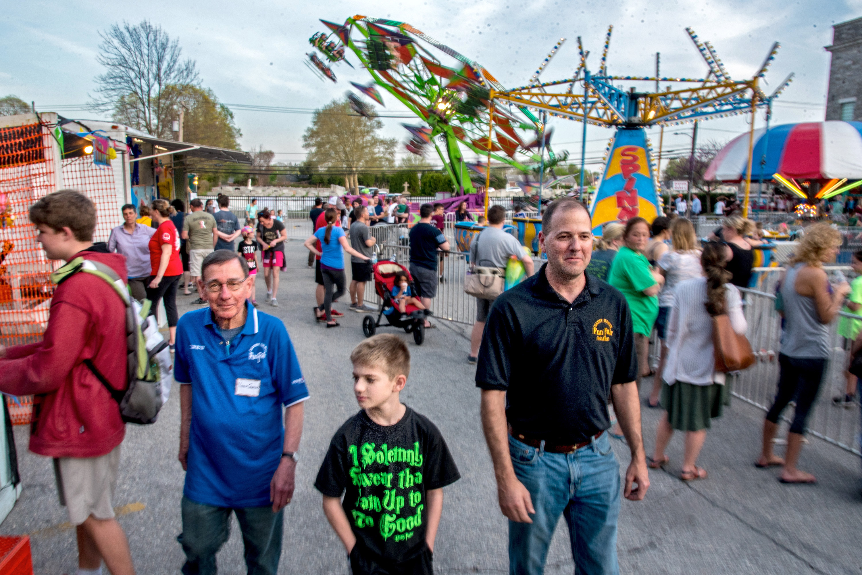 Three generations of Gorskis - Vince, 80; Brogan, 10; and Chris, 46 - walk through the St. Denis Family Fun Fair May 2, 2018. Grandfather and son have helped keep this carnival alive, along with so many others who won´t let it vanish.