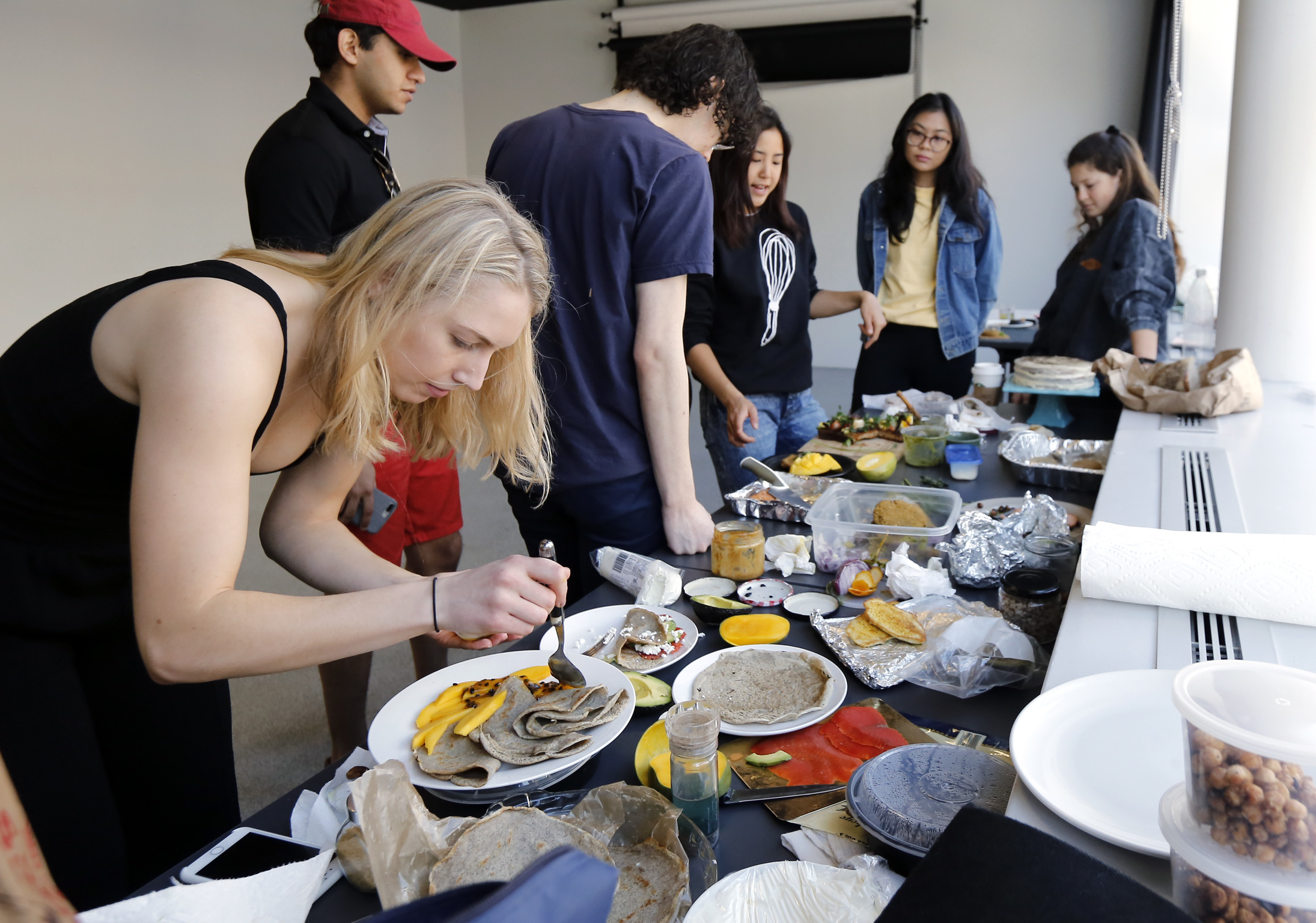 Juliana Sandford (left) and other Penn Appetit members prepare, photograph and eat the food during a photoshoot for an upcoming cookbook at the University of Pennsylvania Fine Arts building.