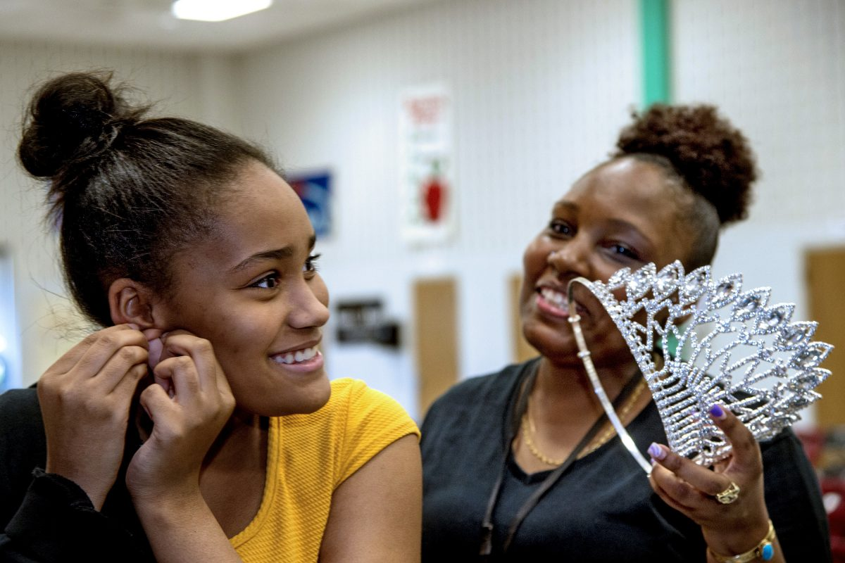 Haneefah McCrary (right) holds the East Coast USA Pageant crown for her daughter Aliyana McCrary, 13, as she puts it on at her William Penn Middle School in Yardley May 1, 2018.