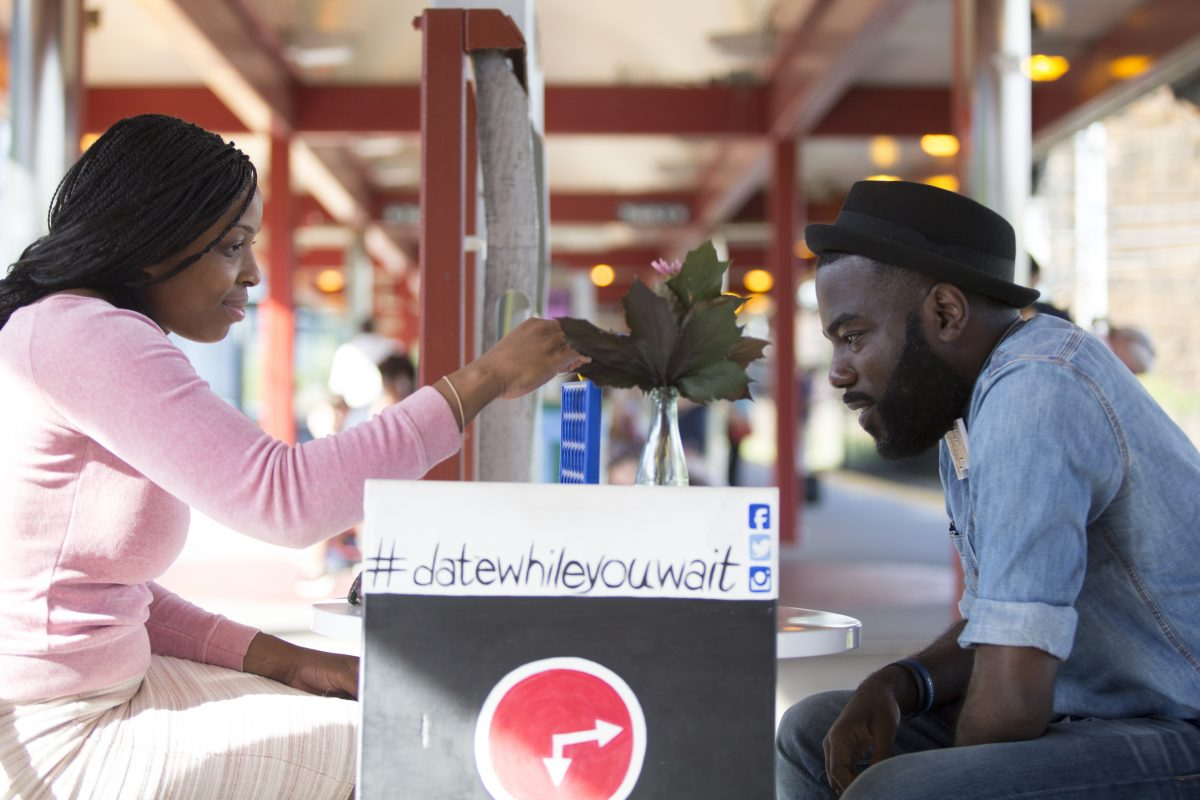 Thomas Knox, creator of Date While you Wait, plays Connect Four with ChiChi Nwadiogbu at the University City SEPTA Regional Rail station. Knox sets up a table with board games and brings it to communities where he would like to connect with people.