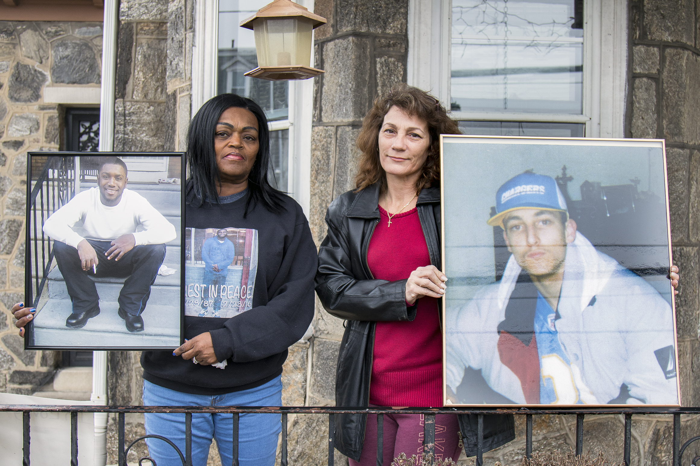 Yullio Robbins (left), and Sophia Fleming (right), both hold up a photo of their sons standing on the porch of Sophia Fleming´s home at the 100 block of West Seymour Street, near Green St, in Philadelphia. Yullio Robbins and Sophia Fleming are two city mothers bonded over the unsolved murders of their sons. When Robbins set up a memorial to her son, killed last year, in front of Fleming´s Seymour Street home, she had no idea that Fleming´s intimately knew her pain. In 2004 Fleming´s teenage son was murdered. The mothers have since bonded. Both cases remain unsolved. Thursday morning, February 23, 2017. ANTHONY BELTRAN / Staff Photographer