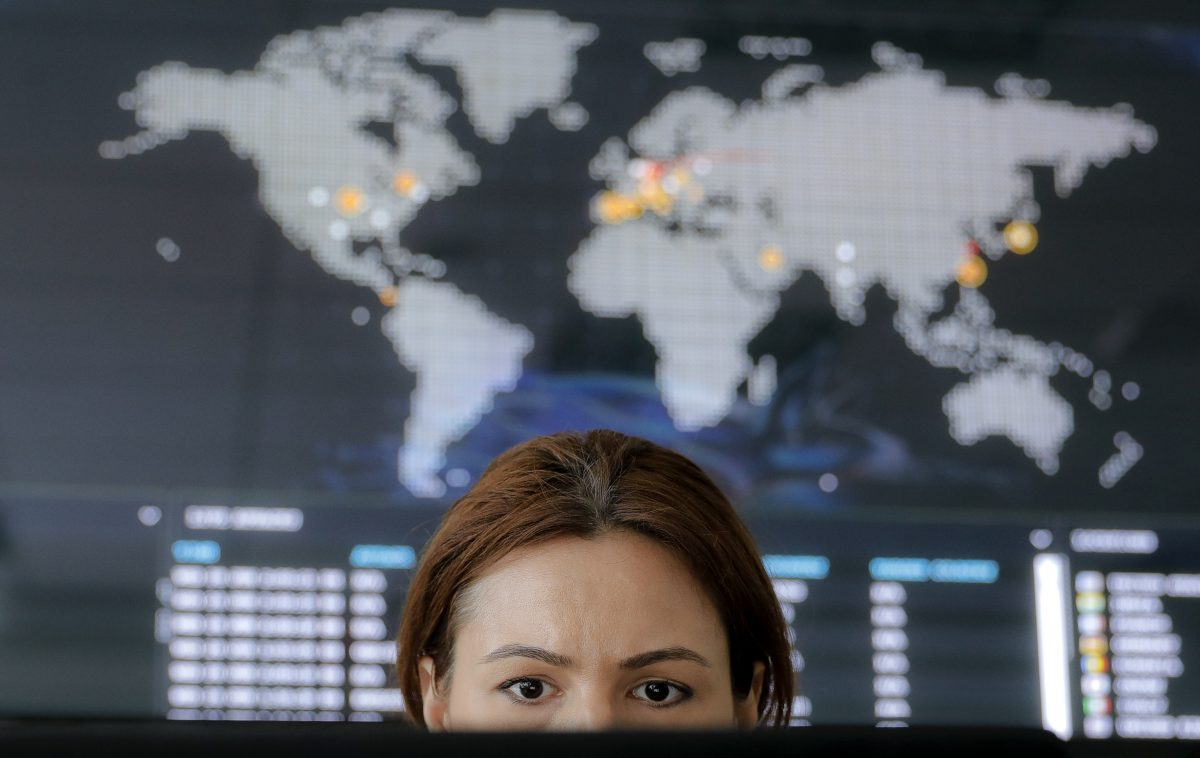 A woman looks at a computer monitor back dropped by a real-time cyber-attacks world map, at the headquarters of Bitdefender in Bucharest, Romania.