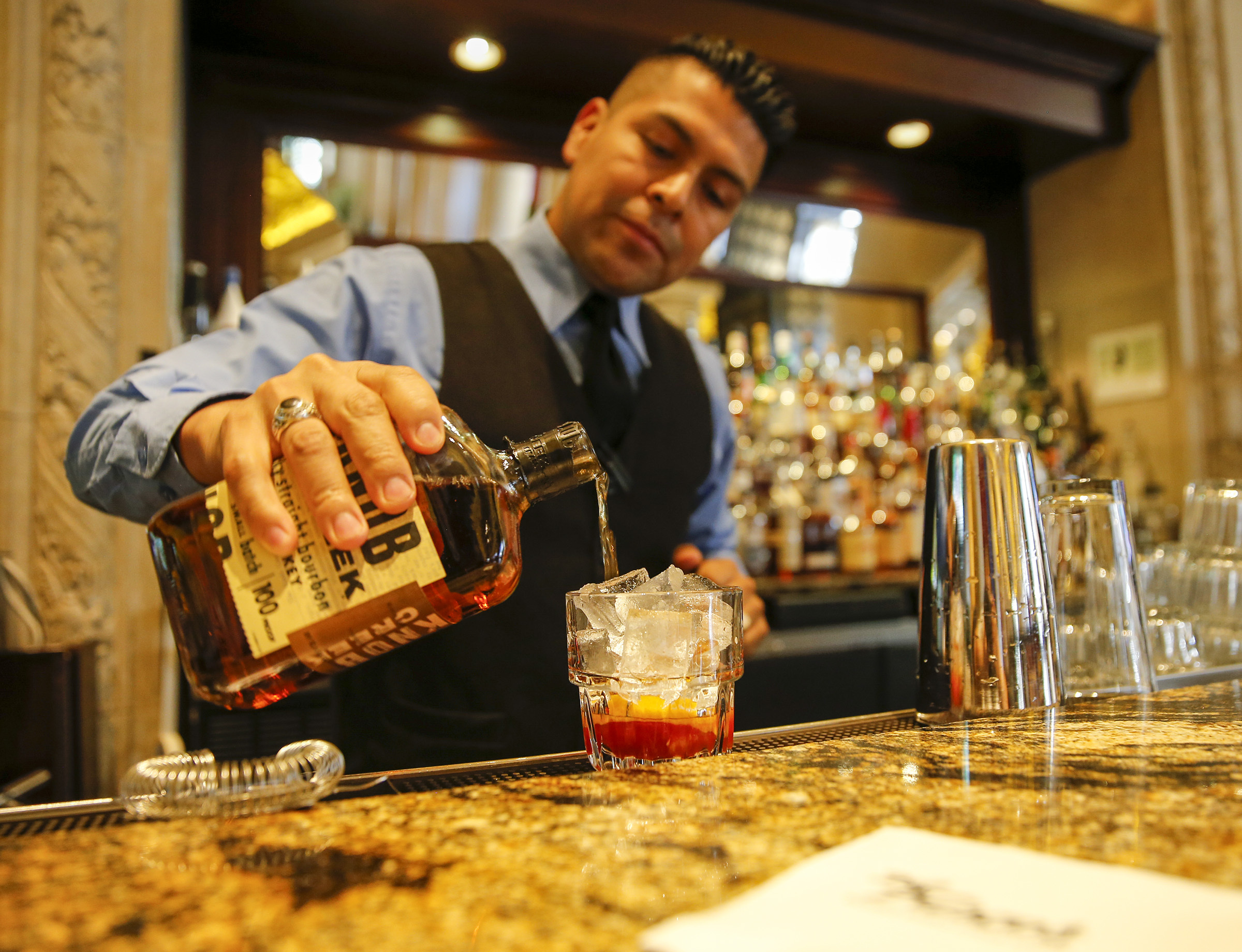 Bartender Juan Moreno pours bourbon while making an old-fashioned.
