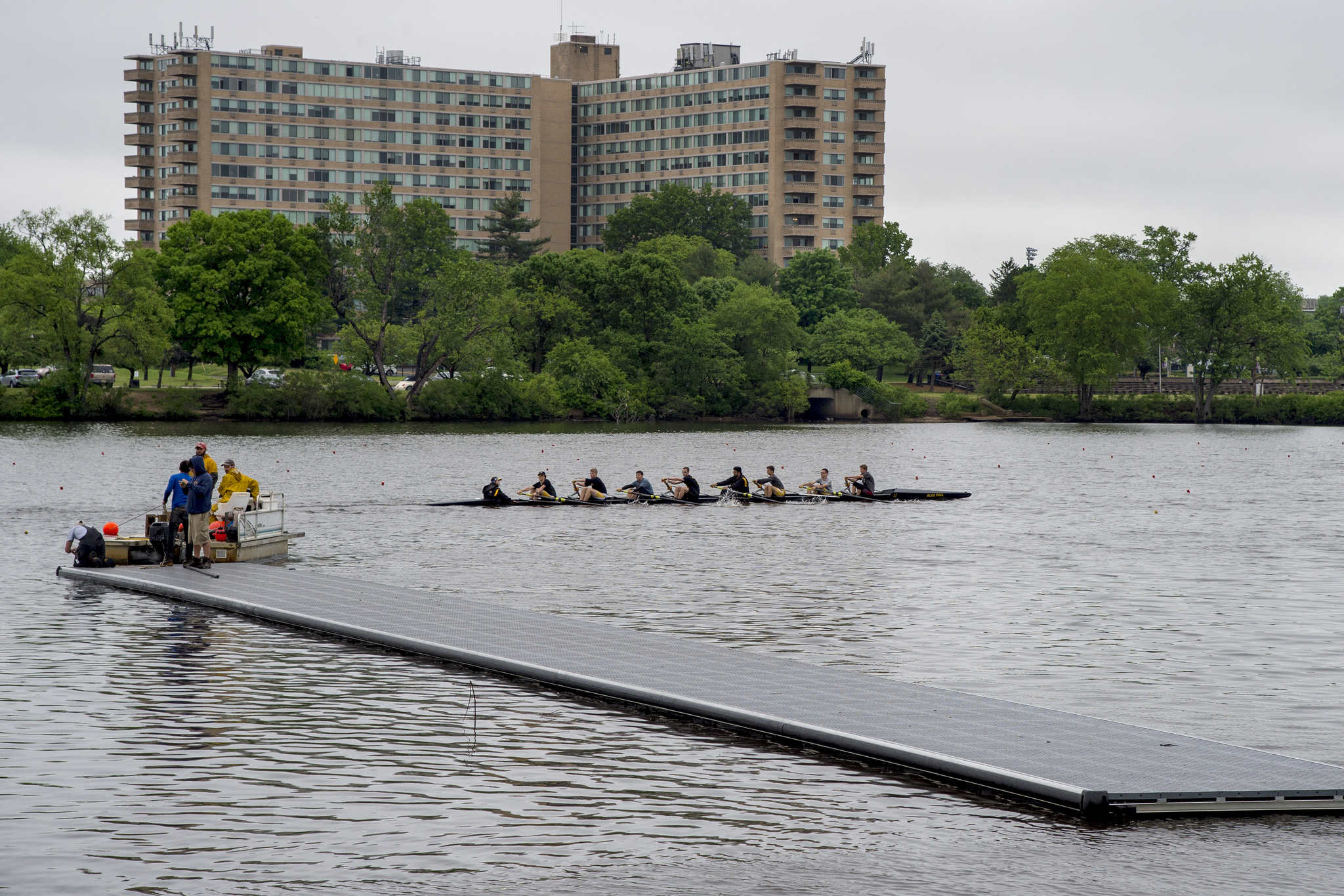 A high school crew team practices as dock sections are floated across the Cooper River.