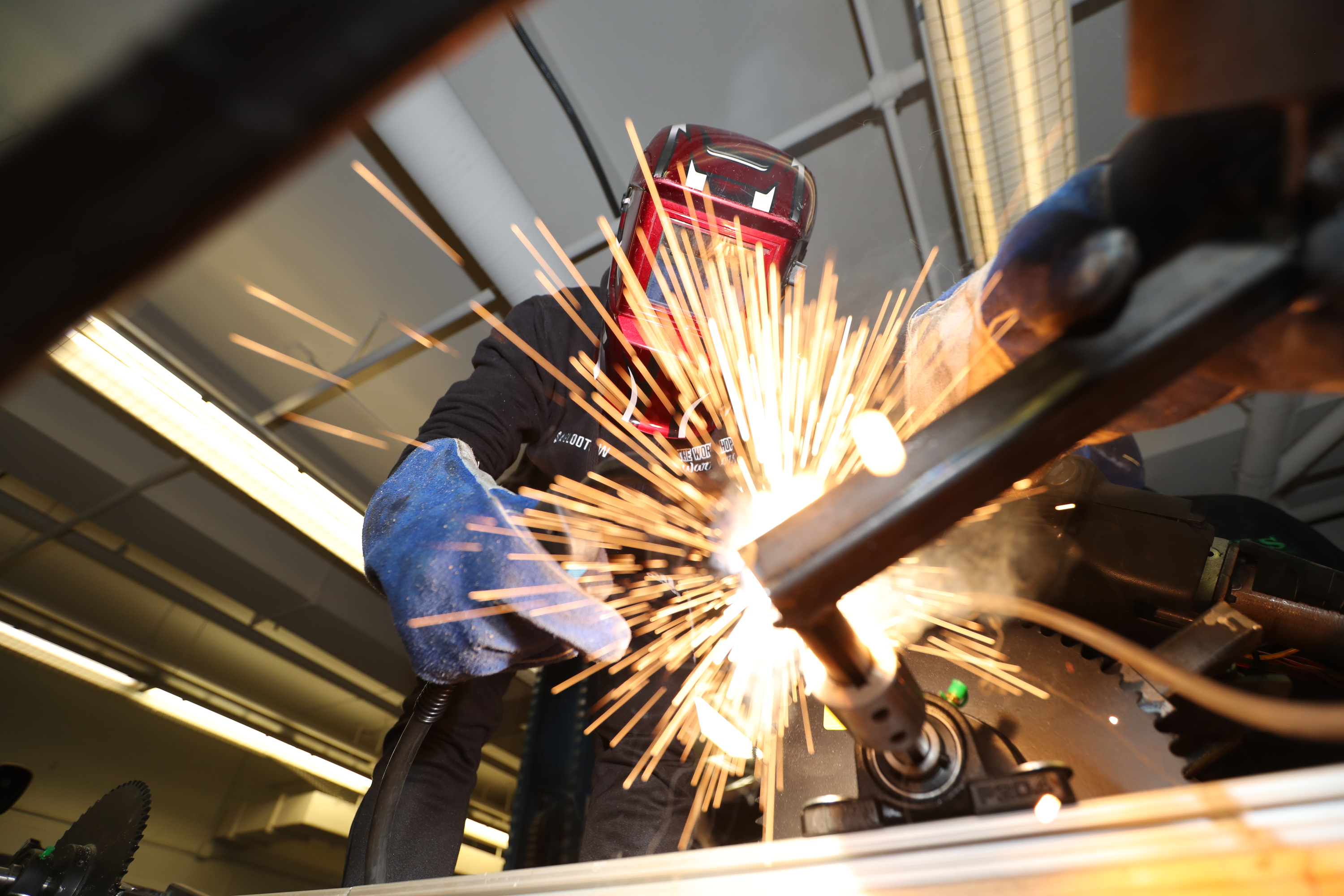 Mang Sang, 17, bead welds a kinetic sculpture at the Workshop School they are building for the Kensington Kinetic Sculpture Derby, Wednesday morning May 16, 2018.