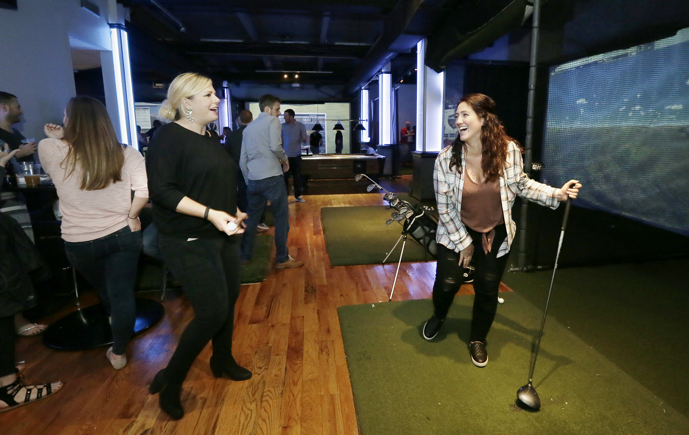Lauren Attanasio (left) and Liz Giunta of Philly dont even play golf, but while attending a birthday party at the club they enjoy the golf simulators upstairs at Golf and Social.