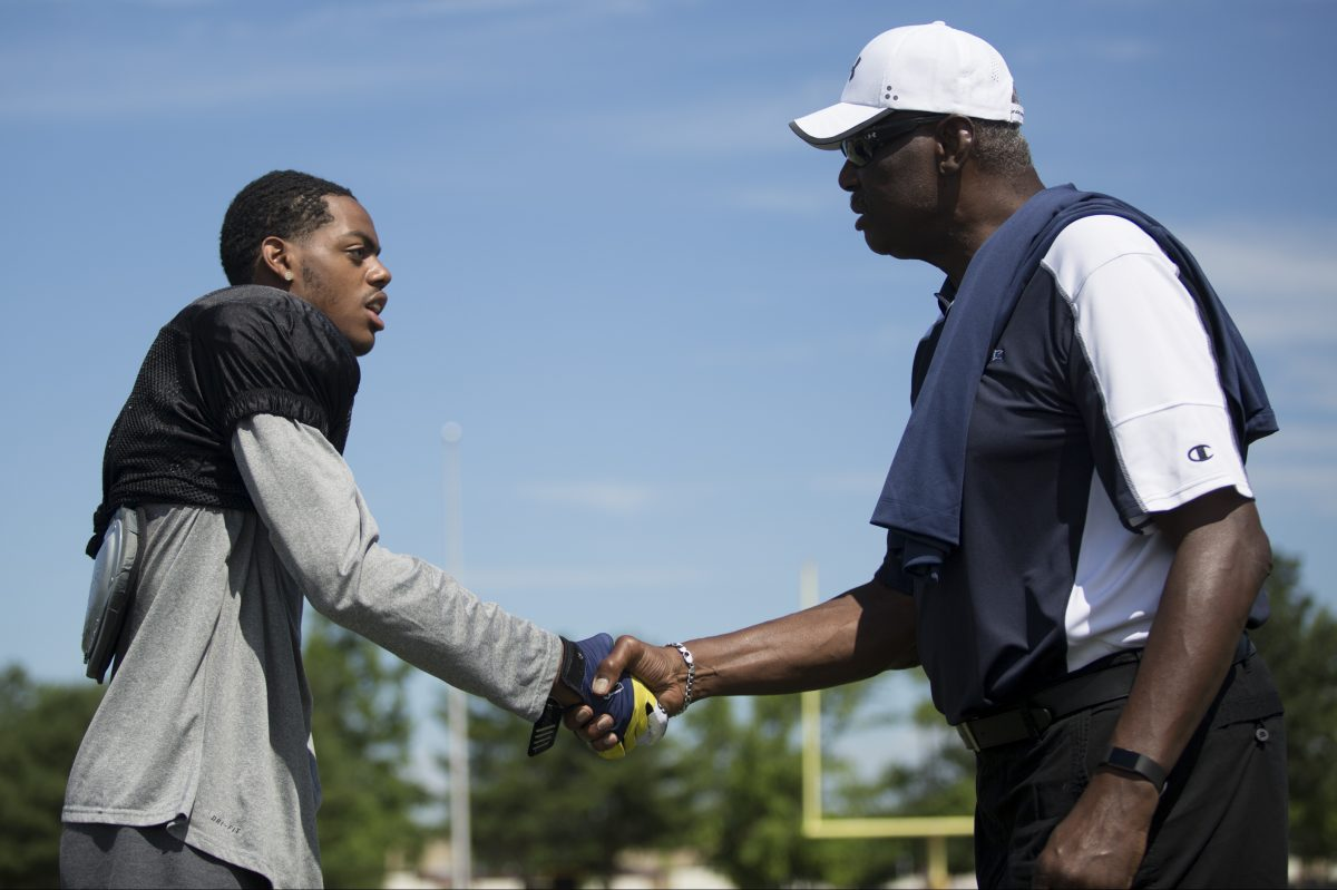 Eagles great , Harold Carmichael, an honorary coach at the Taliaferro Classic, greets Isaiah Anfield of Camden High.