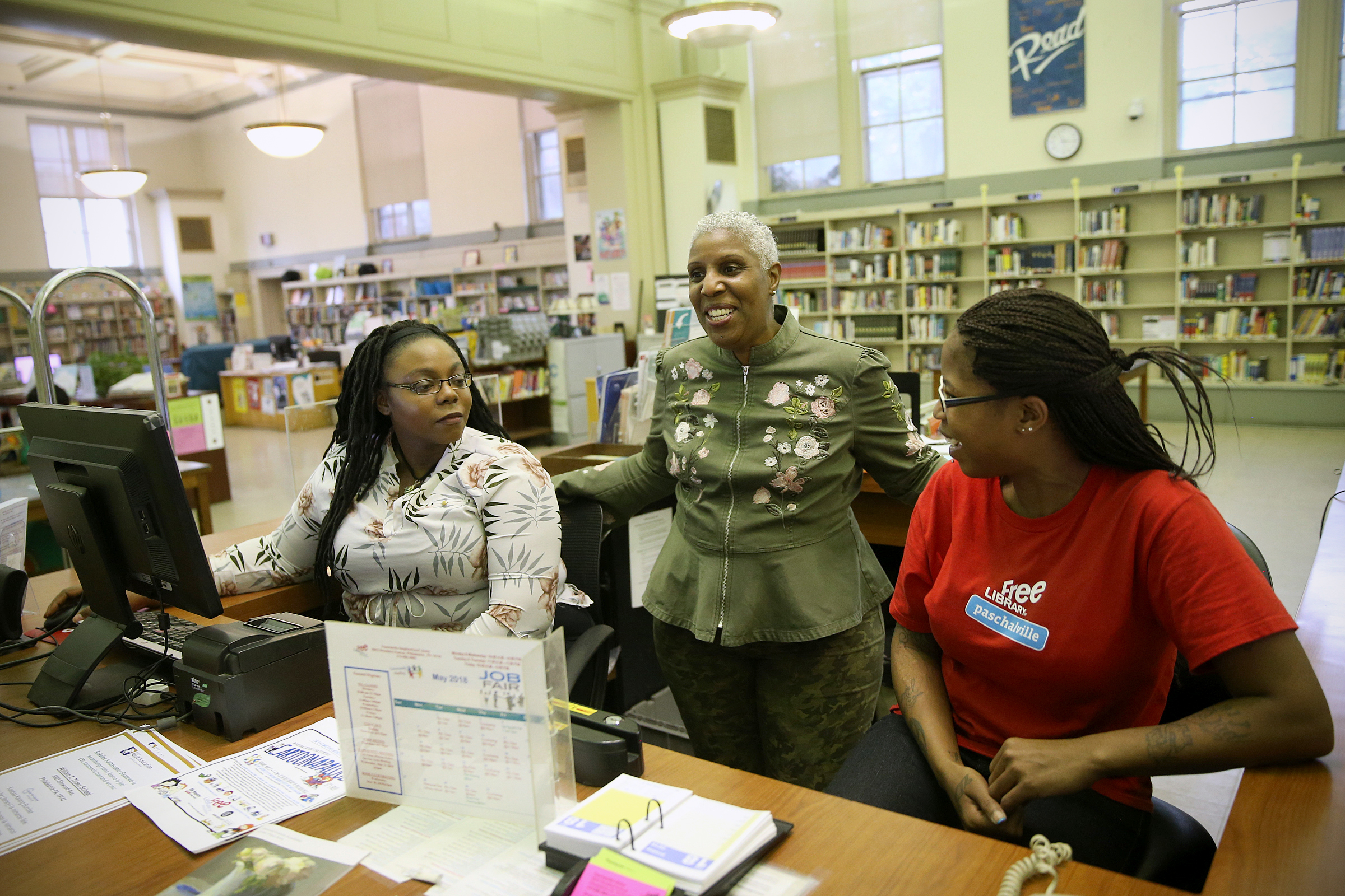 Library supervisor Nyia Morrison, center, talks with library assistants Niema Nelson, left, and Traci Thomas at the Paschalville Library in Southwest Philadelphia on Friday, May 18, 2018. The branch is the only Free Library of Philadelphia location with a job readiness lab, which helps community members find and apply to jobs.