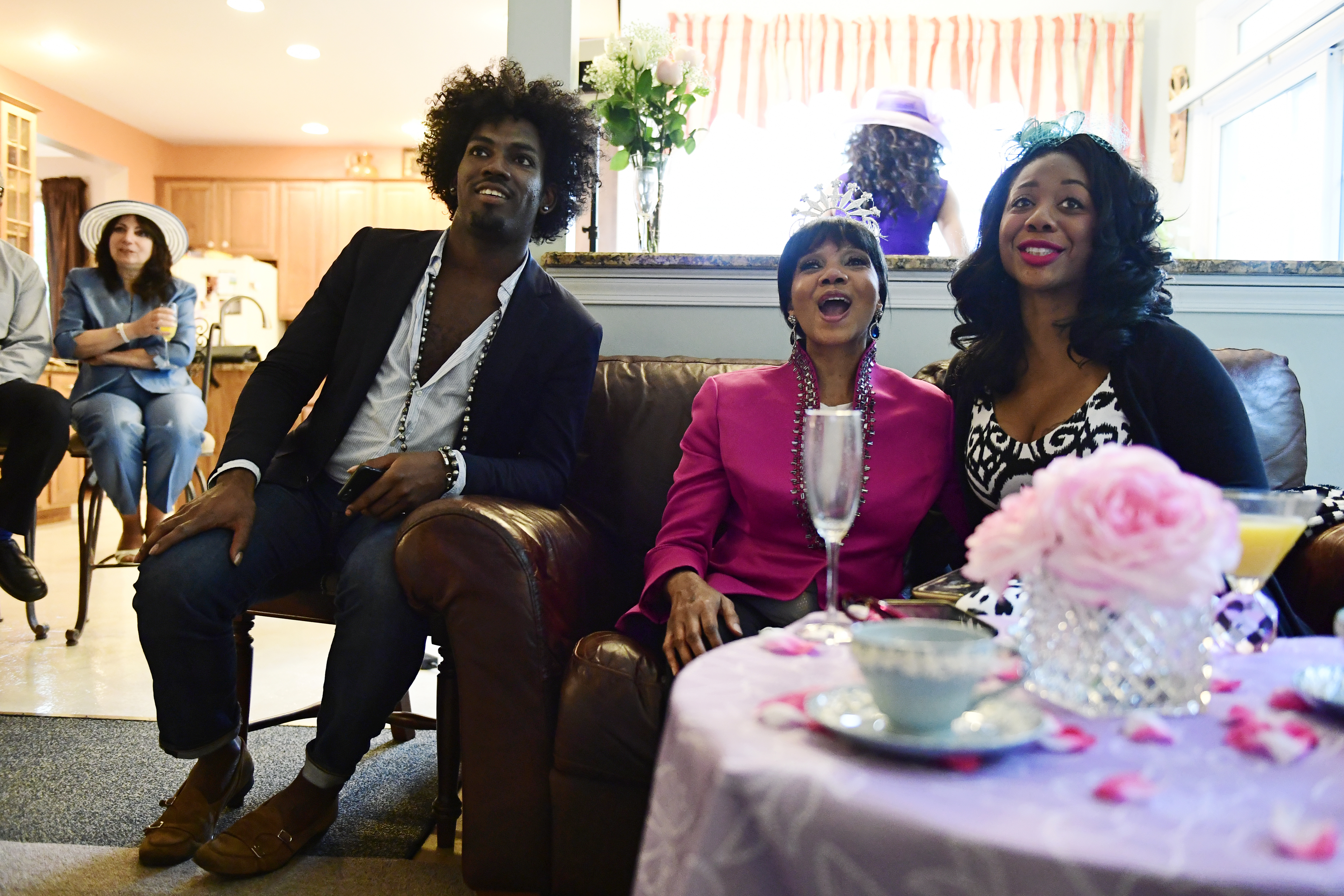 From left, David Alexander Jenkins, Paula Jackson and Cherri Gregg, all of Philadelphia, react during a television viewing party of the royal wedding of Meghan Markle and Prince Harry, Saturday, May 18, 2018, at the Armstrong-Turner residence in Burlington, N.J. The ceremony married the pomp and circumstance of Britain´s most sacred institution with elements of black culture, drawing viewers not normally drawn to the spectacle of the monarchy. (AP Photo/Corey Perrine)