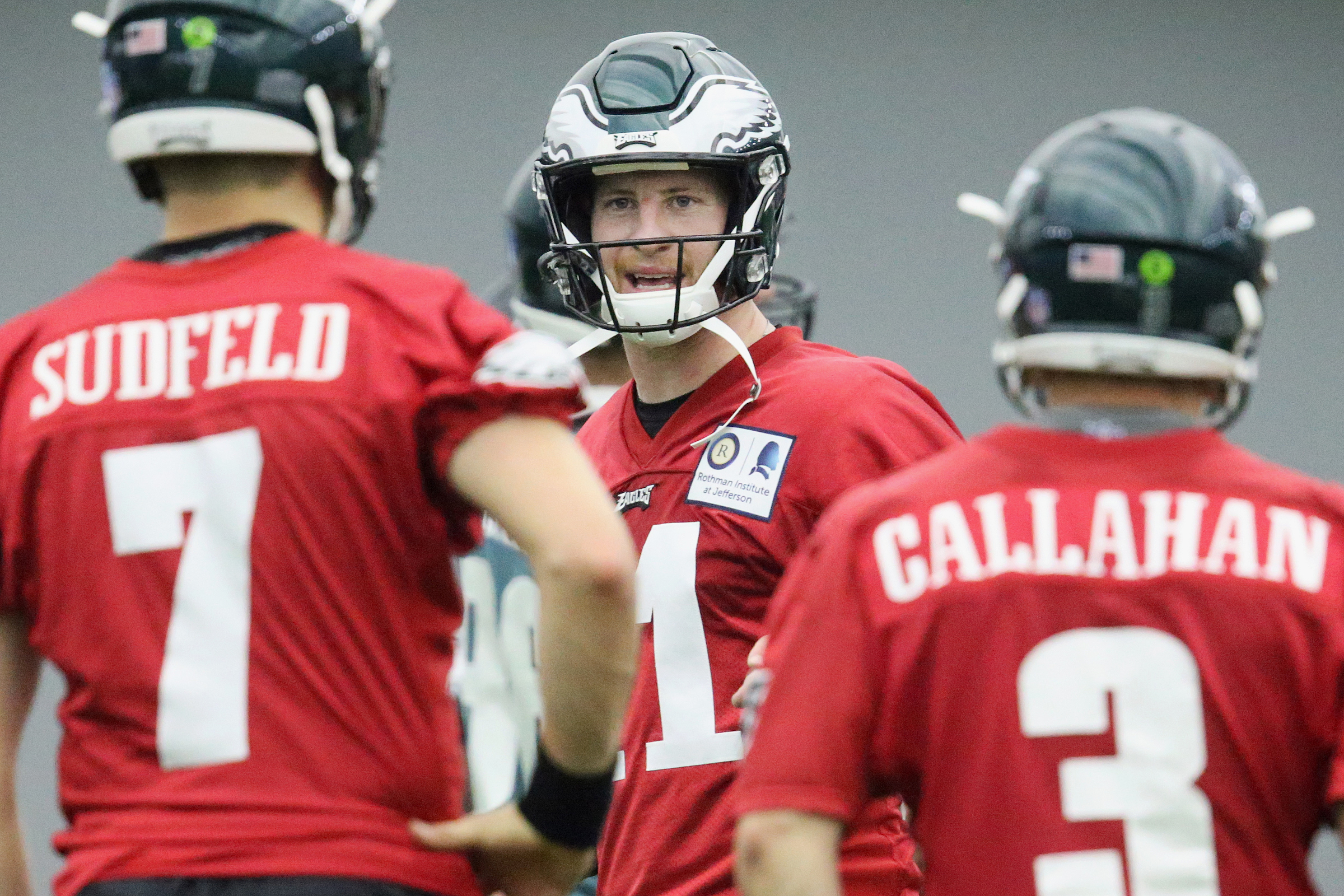 Eagles quarterback Carson Wentz (11) talks to backups Nate Sudfeld (7) and Joe Callahan (3) during practice at the NovaCare Complex on Tuesday.