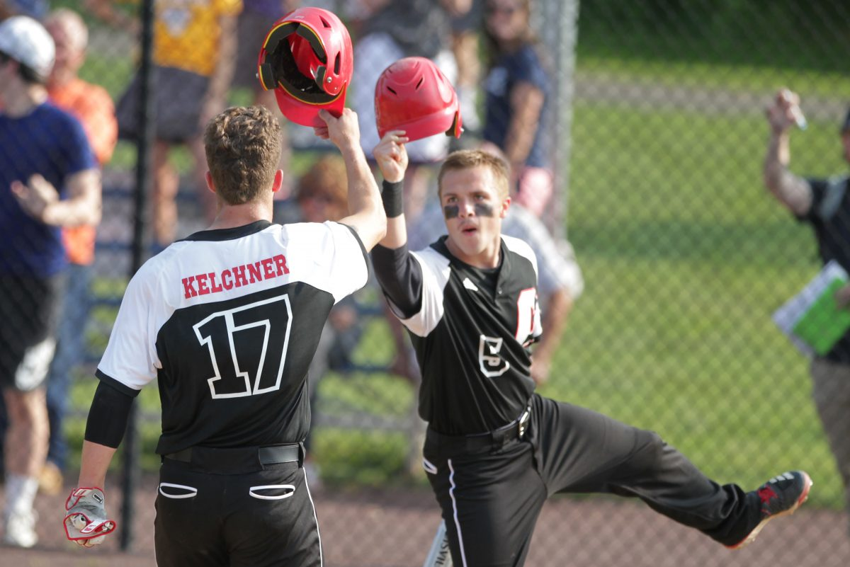 Jake Kelchner (left) and Cole Chesnet of Archbishop Carroll celebrate after Kelchner hit a two-run home run against Cardinal OHara.
