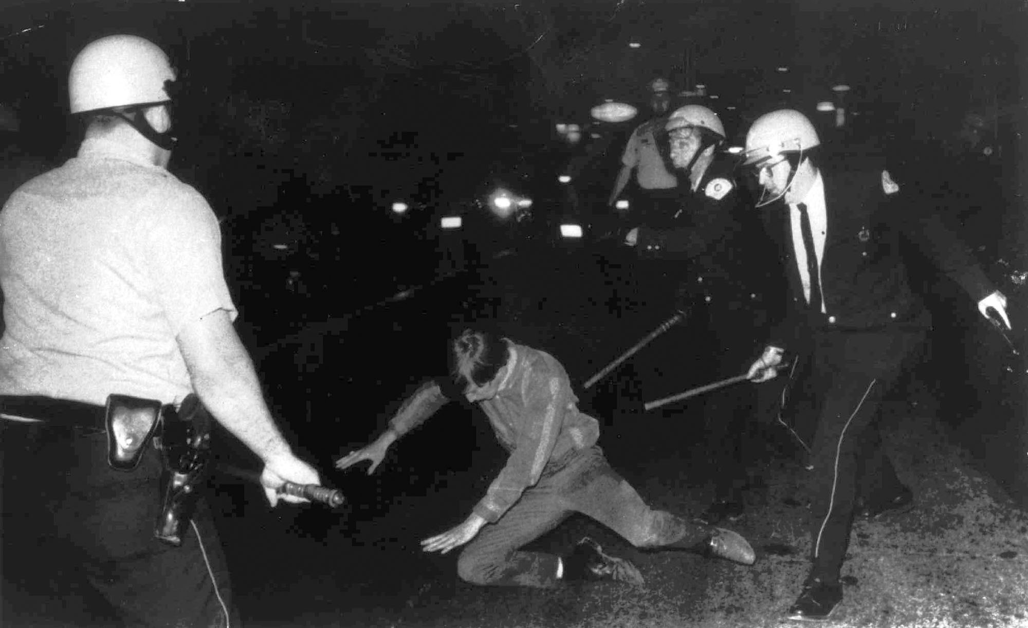 An Aug. 27, 1968 photo shows a demonstrator falling to the ground as he is pursued by Chicago Police officers during the Democratic National Convention in Chicago.