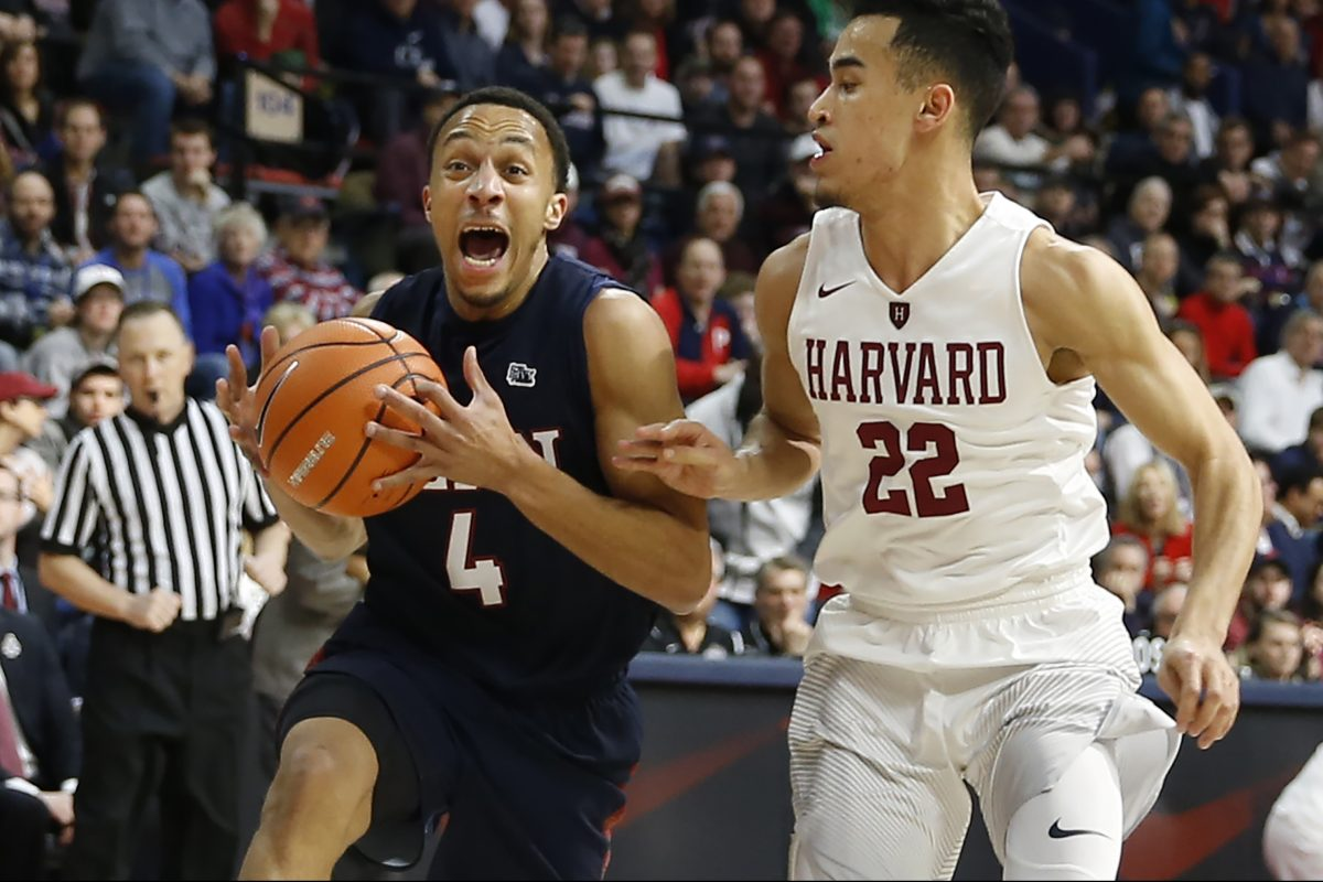 Penn's Darnell Foreman drives past Harvard's Christian Juzang during the championship of this year's Ivy League tournament at the Palestra.