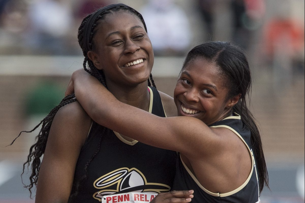 Neumann-Goretti's Arianna Ruffin (right) hugs anchor Sydni Townsend after they won the 4×400 relays at last year's Philadelphia Catholic League championship race at the Penn Relays.