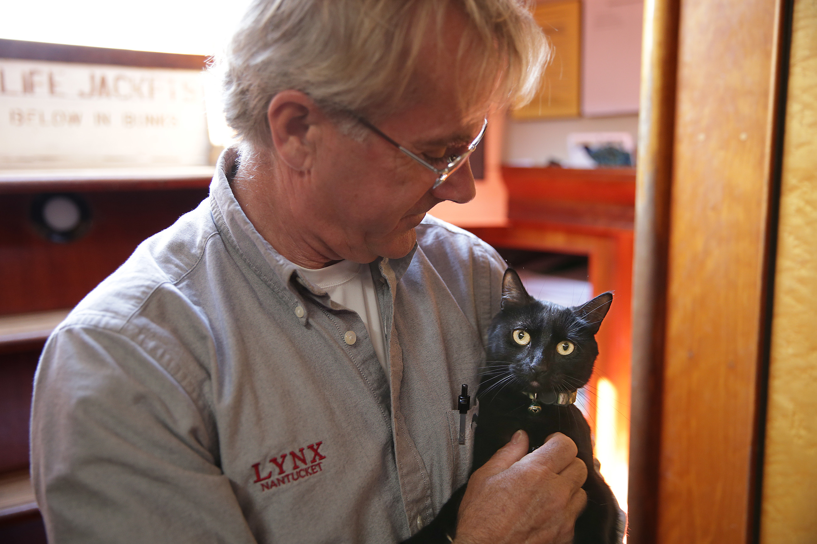 Capt. Donald Peacock, holds Leeloo, the ship's cat, below the deck on the Lynx tall ship at Penn´s Landing