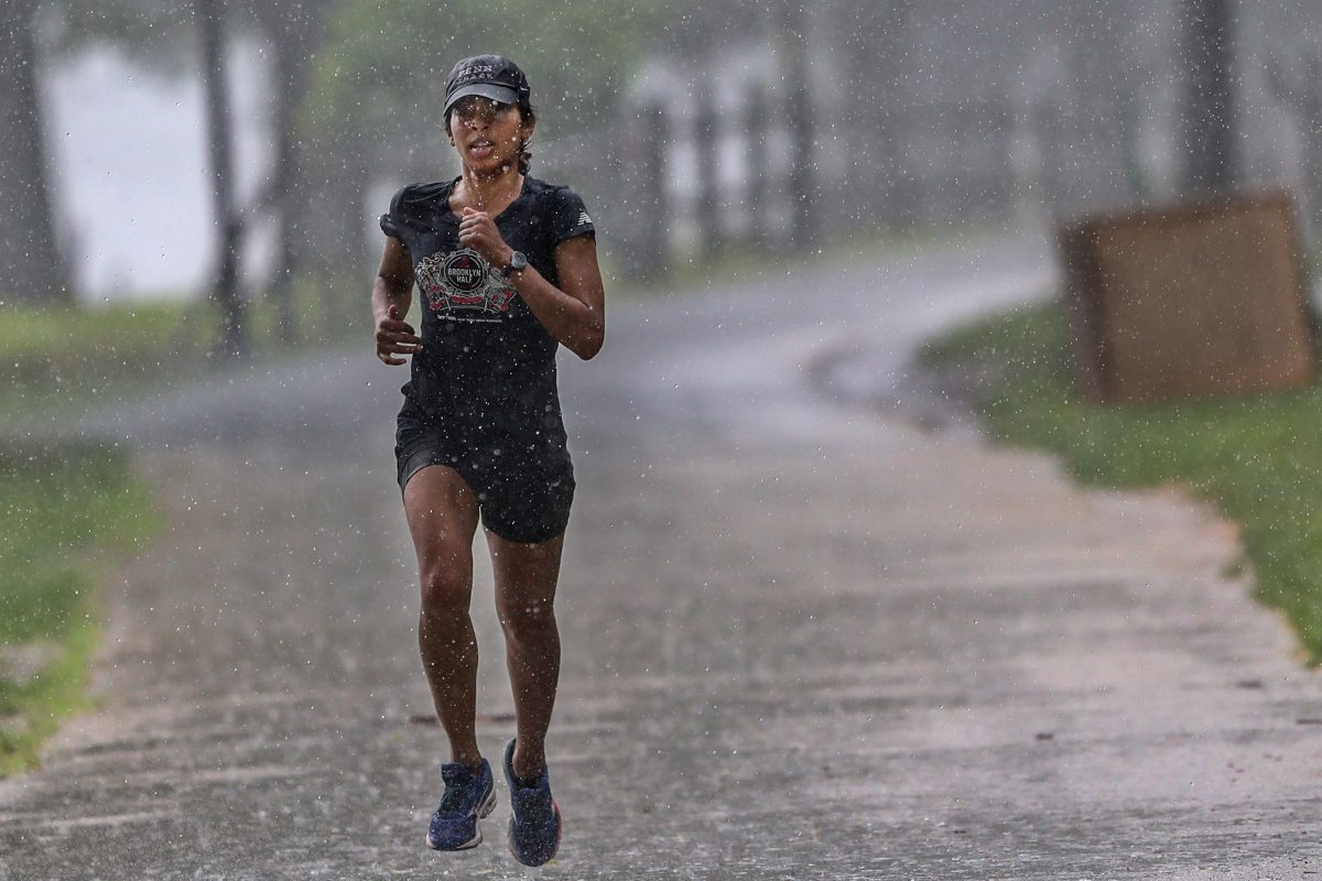 A jogger slogs through pouring rain early Sunday morning in Fairmount Park.