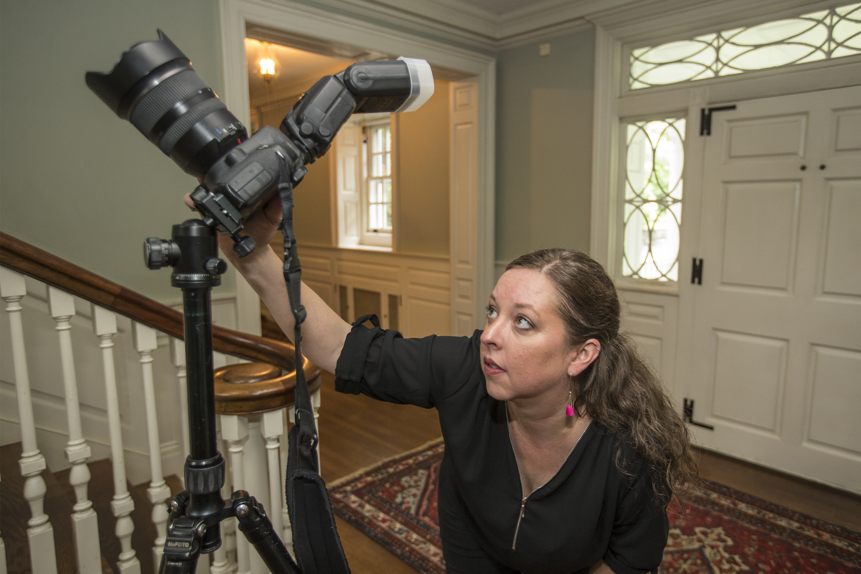 Real Estate photographer Kate Devlin looks at the back of her Canon digital slr, at the LED screen, to make sure her exposure of the staircase in a Glenside home for sale, is correct.