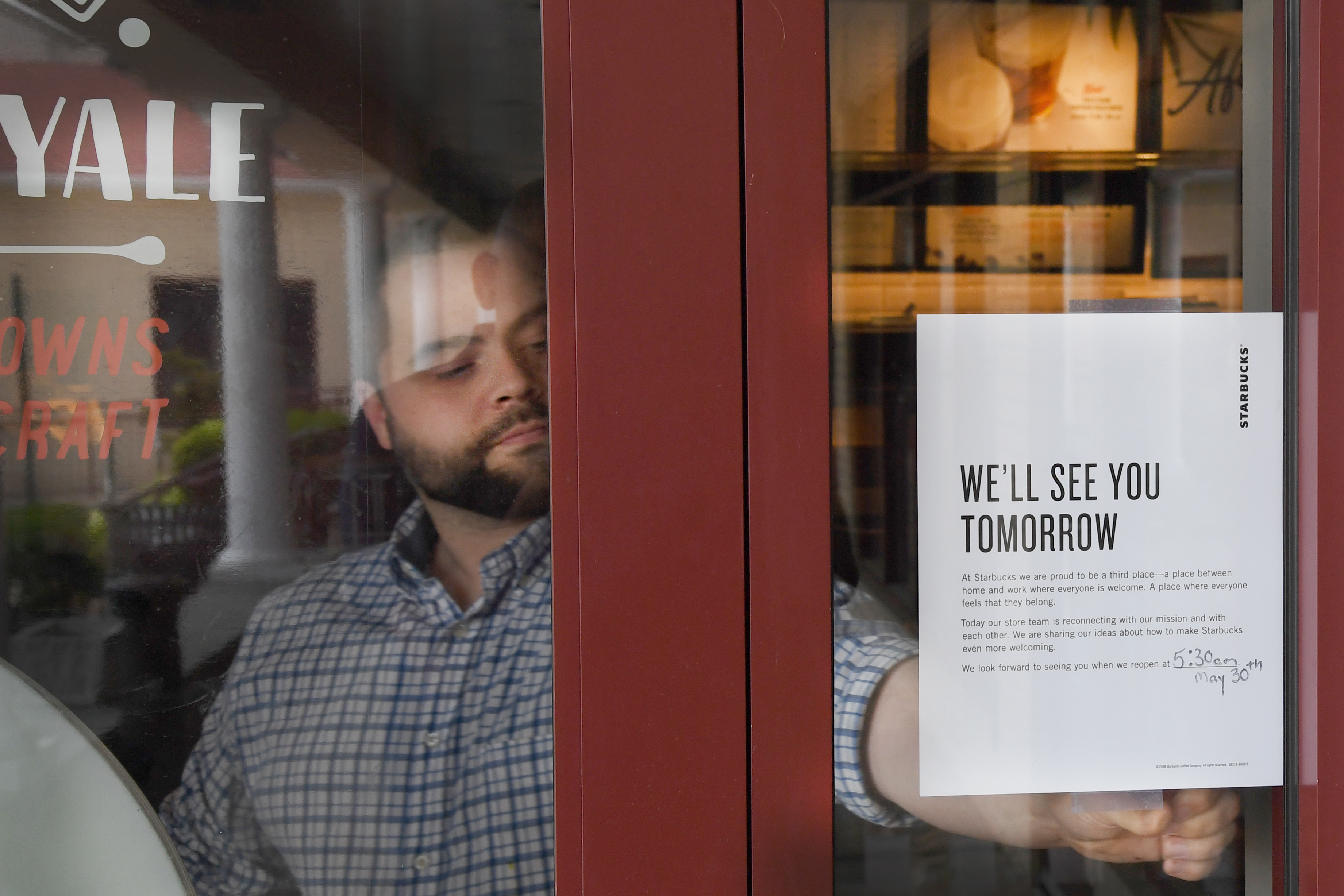 A Starbucks staff member tapes a message to the door of the Starbucks on Bala Cynwyd, letting customers know that the store will be closed the rest of the day, on Tuesday May 29, 2018, as part of Starbucks´ new implicit bias training.
