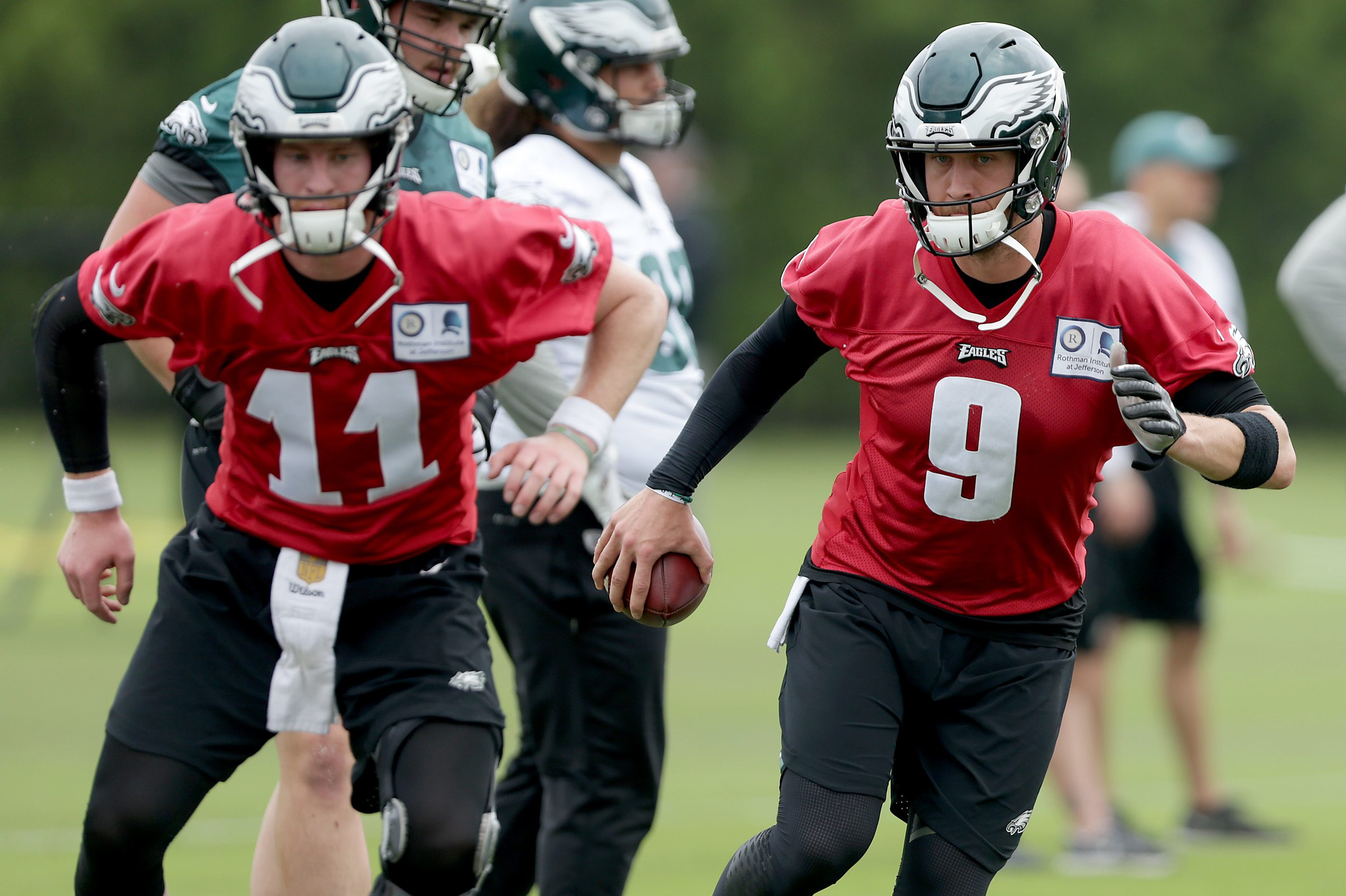 Eagles' Carson Wentz, left, and Nick Foles, right, warm up as the Eagles hold OTA´s at the NovaCare Complex in Philadelphia, PA on May 29, 2018.