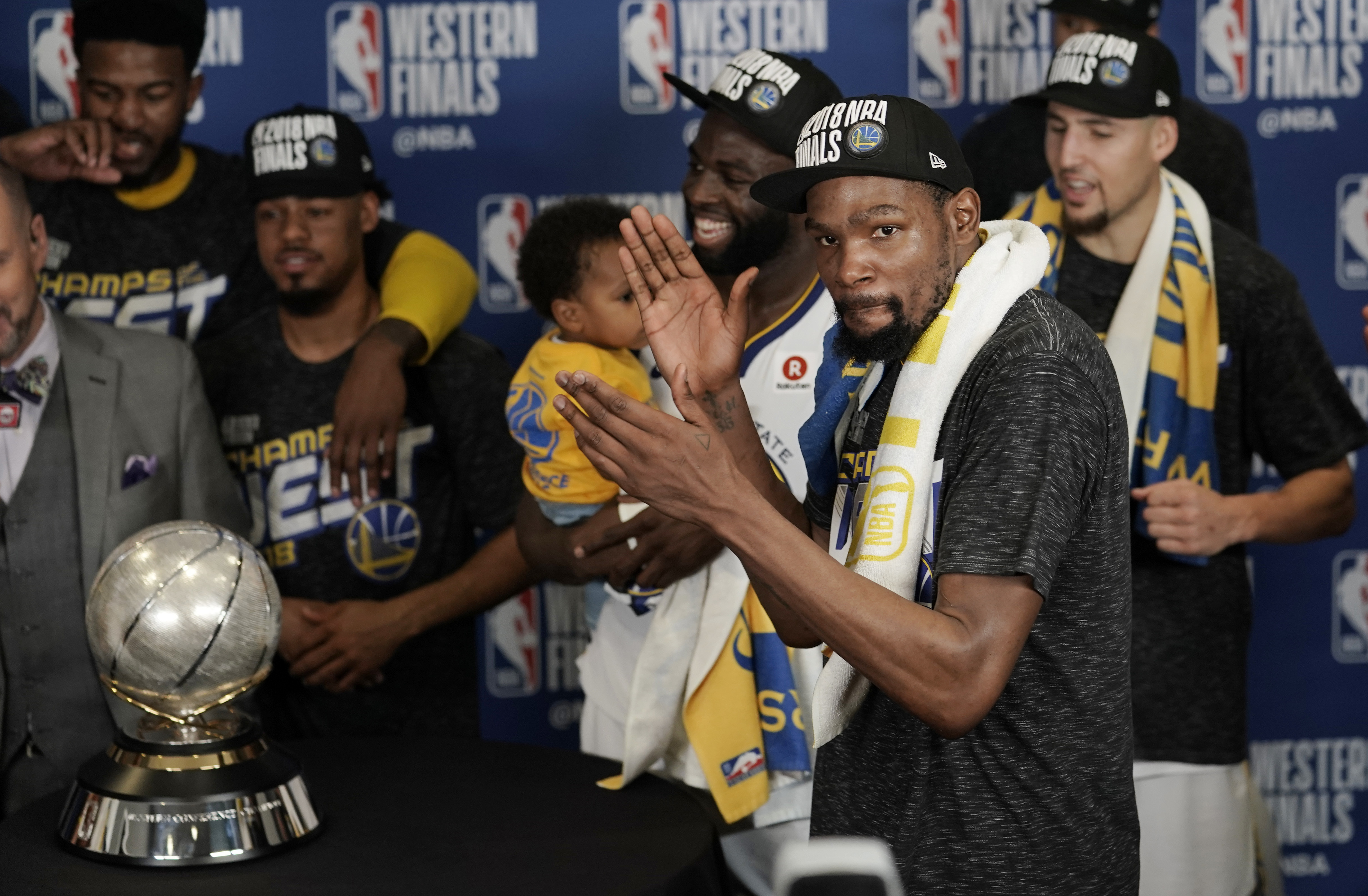 Golden State Warriors forward Kevin Durant celebrates with teammates as they receive their trophy after defeating the Houston Rockets in Game 7 of the NBA basketball Western Conference finals, Monday, May 28, 2018, in Houston.