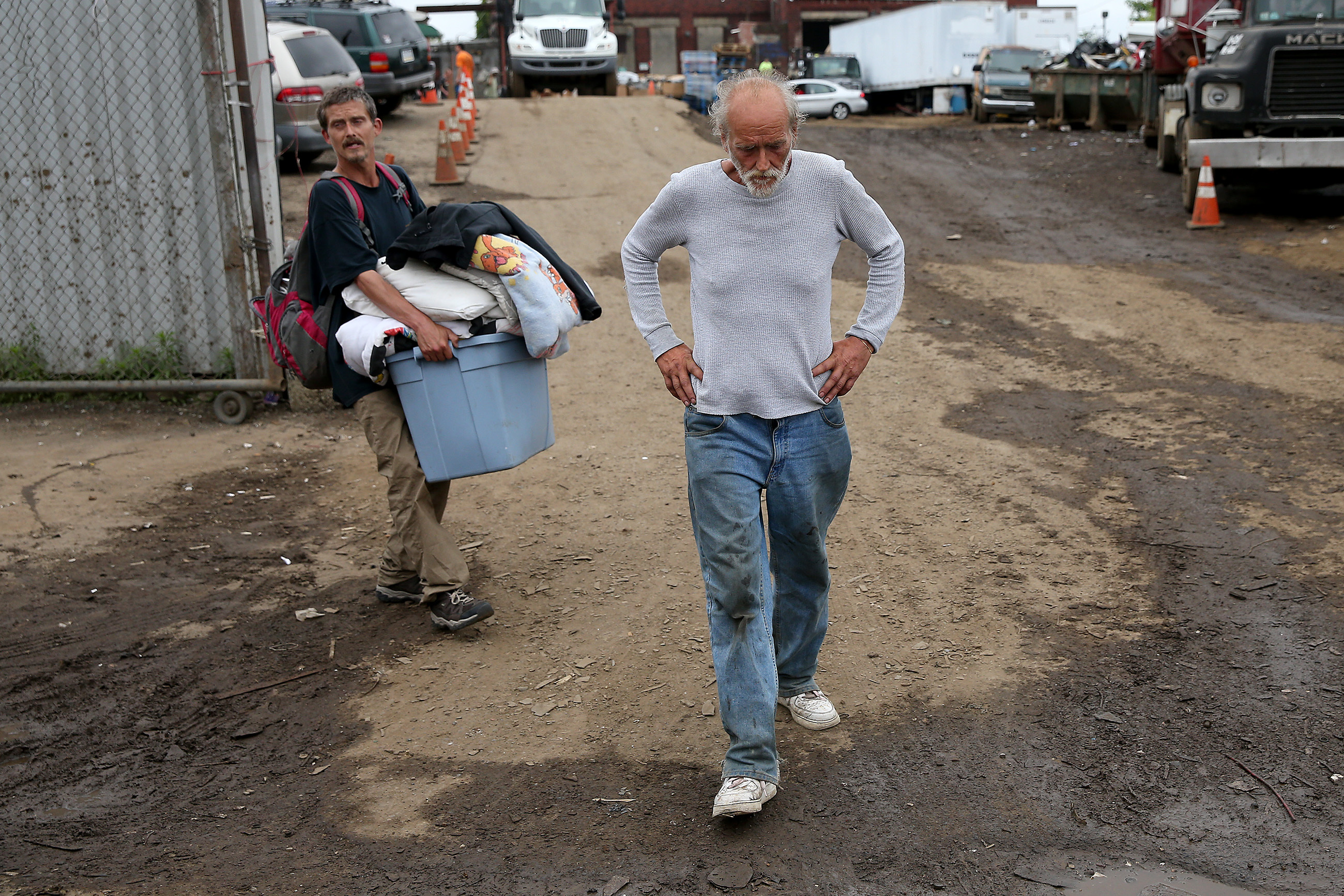 Jason Carmine, left, and his father, Kevin Carmine, right, who were living under the Tulip Street bridge, carry away their belonging as police evicted people living at two of Kensington´s heroin camps in Philadelphia, PA on May 30, 2018. DAVID MAIALETTI / Staff Photographer
